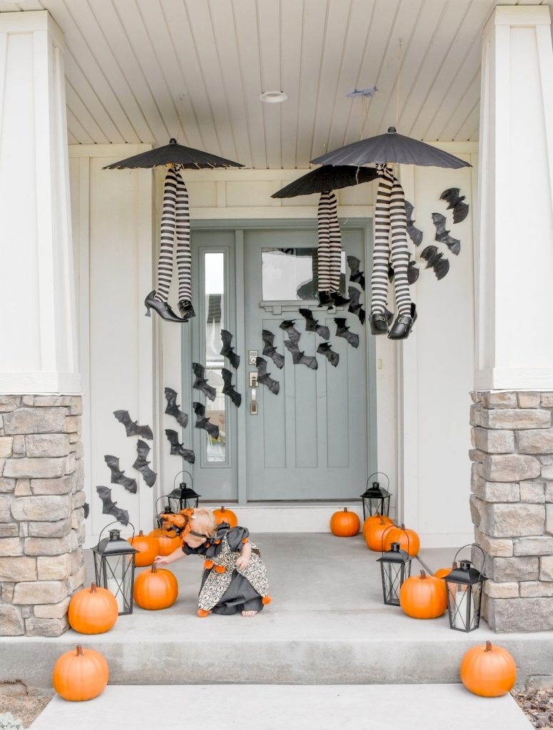 Halloween porch decorations with witch legs, bats and pumpkins