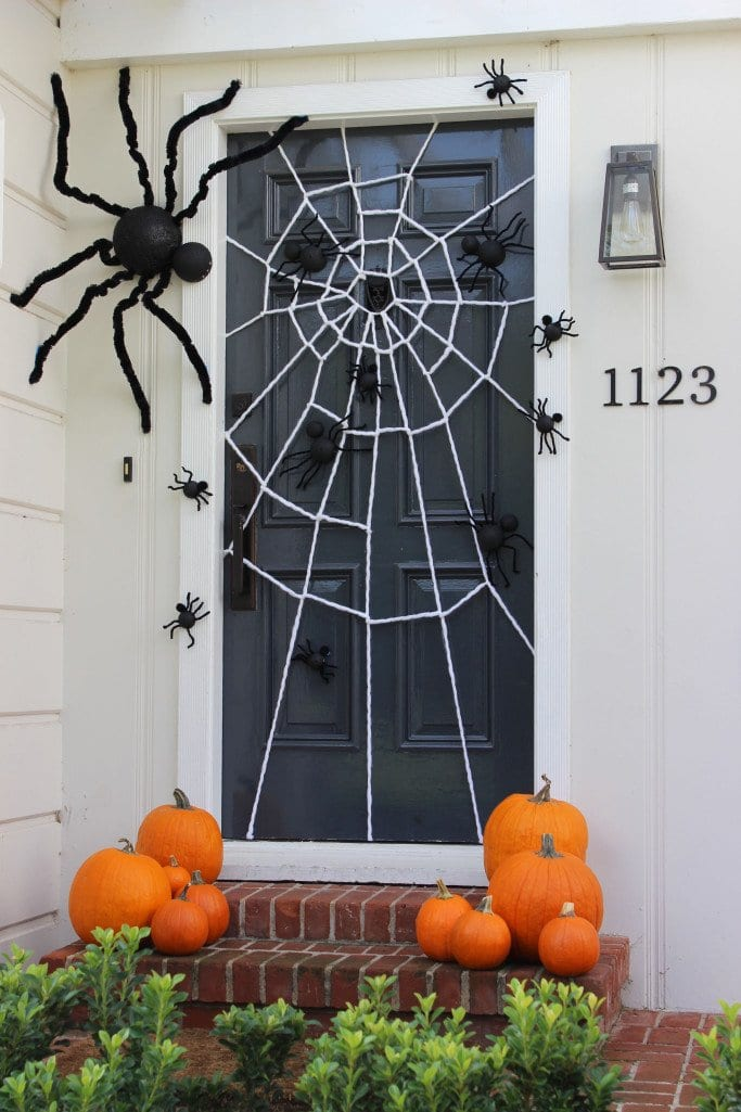 Decorate your porch with spiders and a spiderweb for Halloween