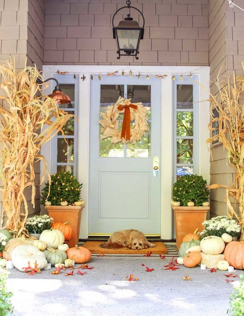 Decorate your fall porch with corn stalks, pumpkins, and a wreath