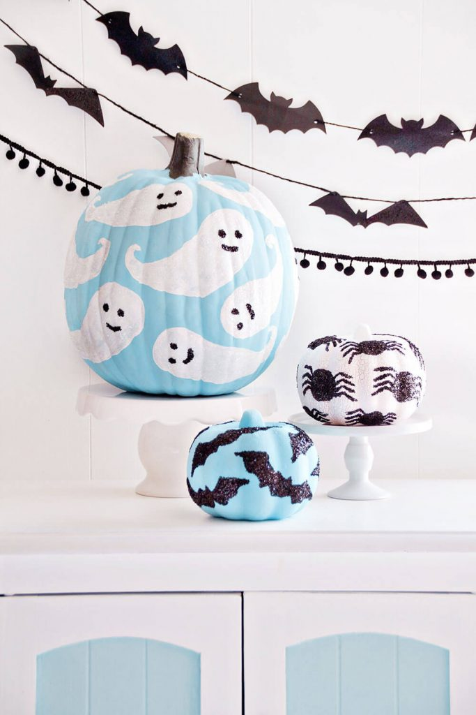 Paint pumpkins for Halloween with spiders, ghosts, and bats on them.