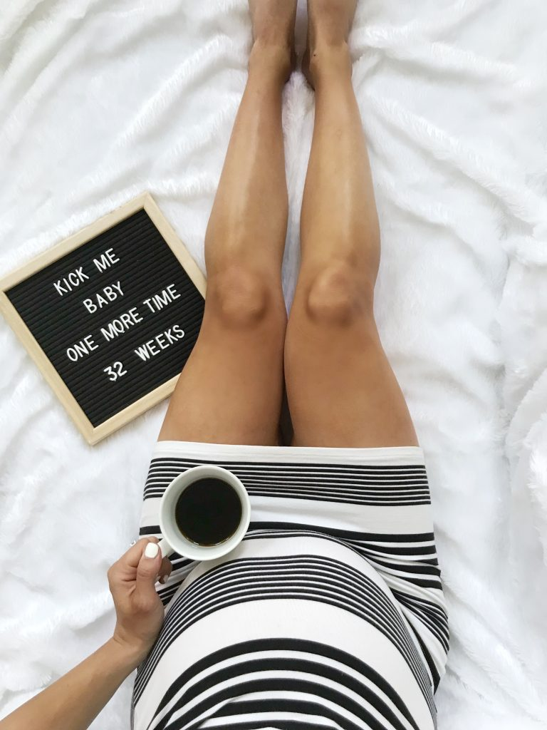 "Letter board that says ""kick me baby one more time 32 weeks"""