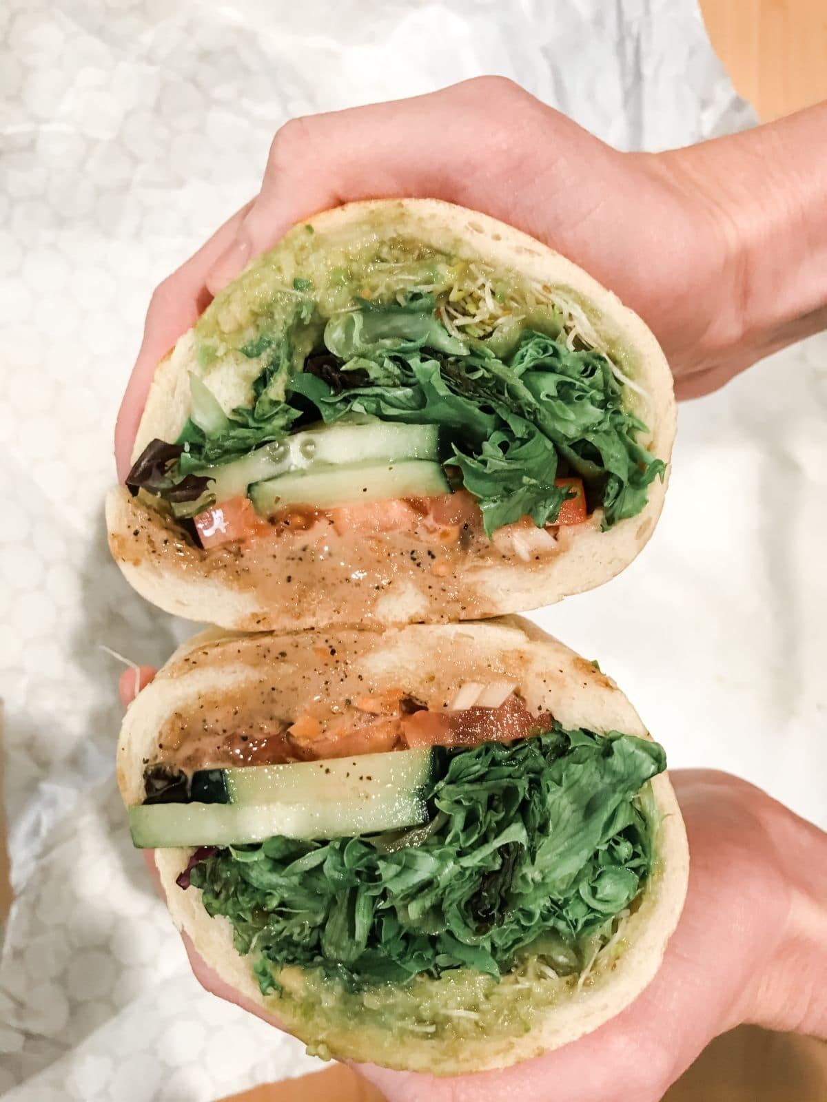 fresh veggie sandwich from buds with cucumber, lettuce, tomato, avocado, sprouts, and house vinaigrette being held up in a persons hands