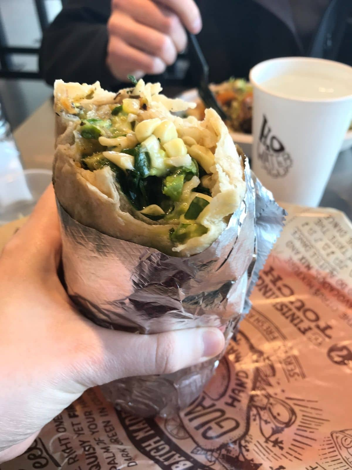 chipotle veggie burrito wrapped in foil and being held up with a water cup in the background