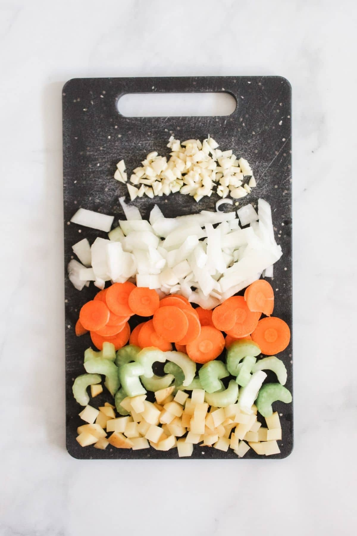 chopped up onions, garlic, carrots, potatoes, and celery on black cutting board