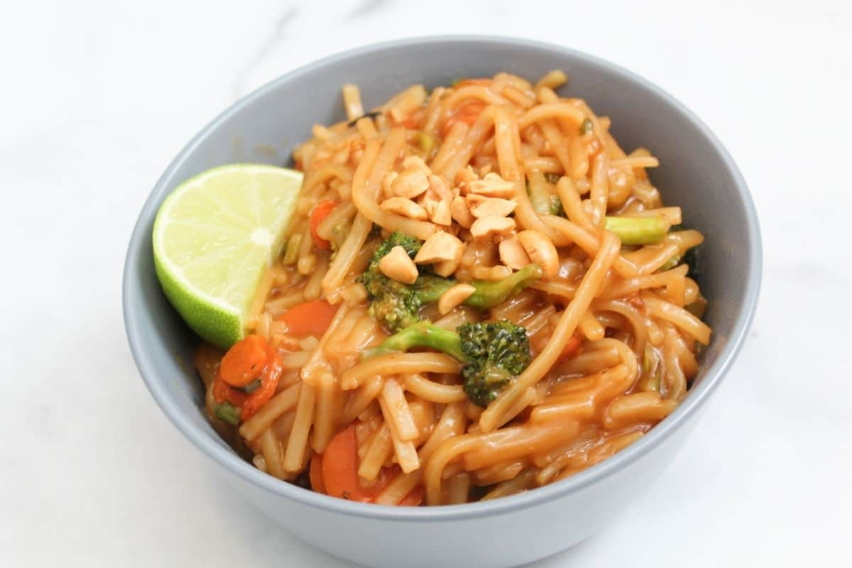 finished pad thai dish topped with chopped peanuts and lime wedge