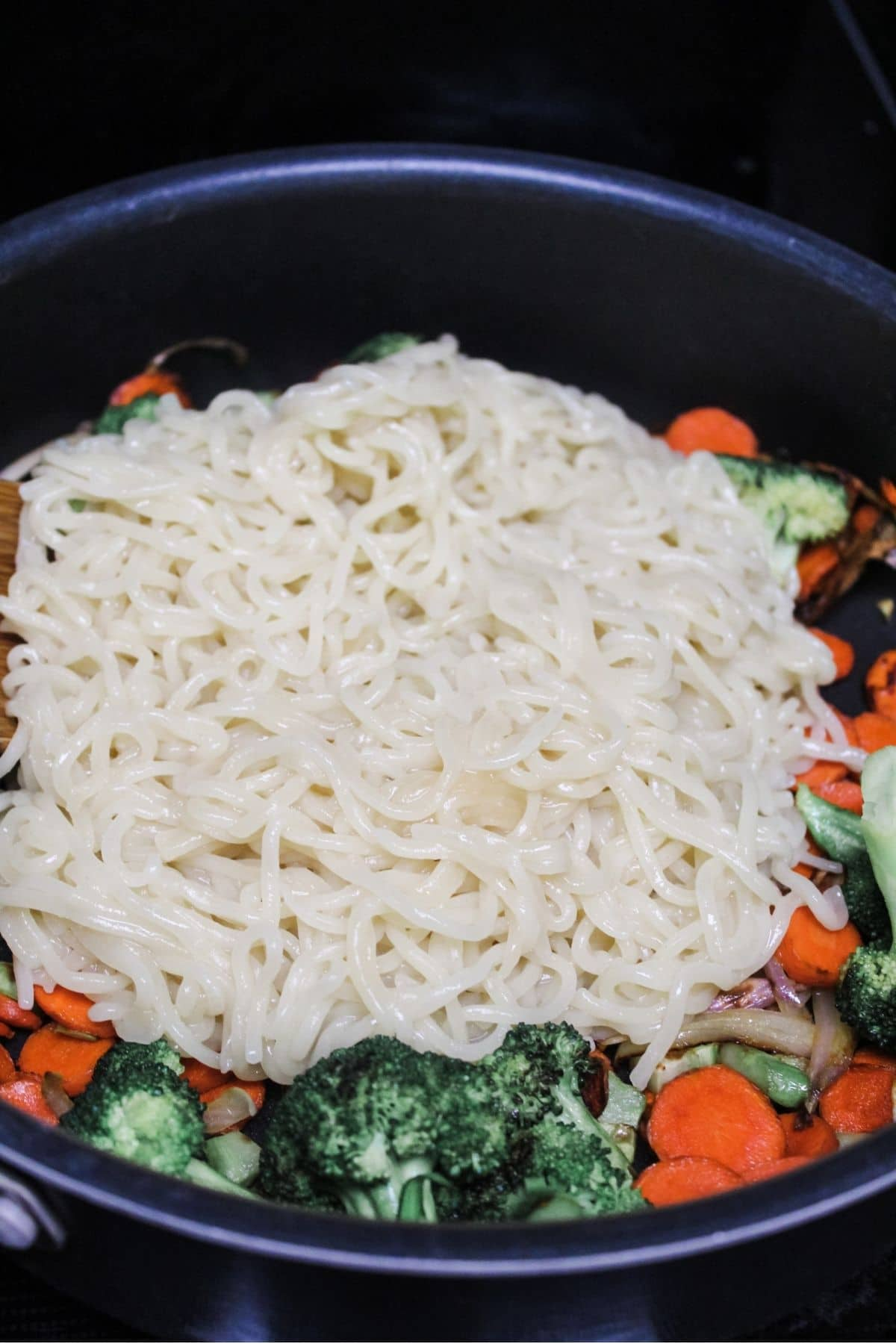 combining cooked ramen noodles with broccoli, carrots, and shallots in a big pan