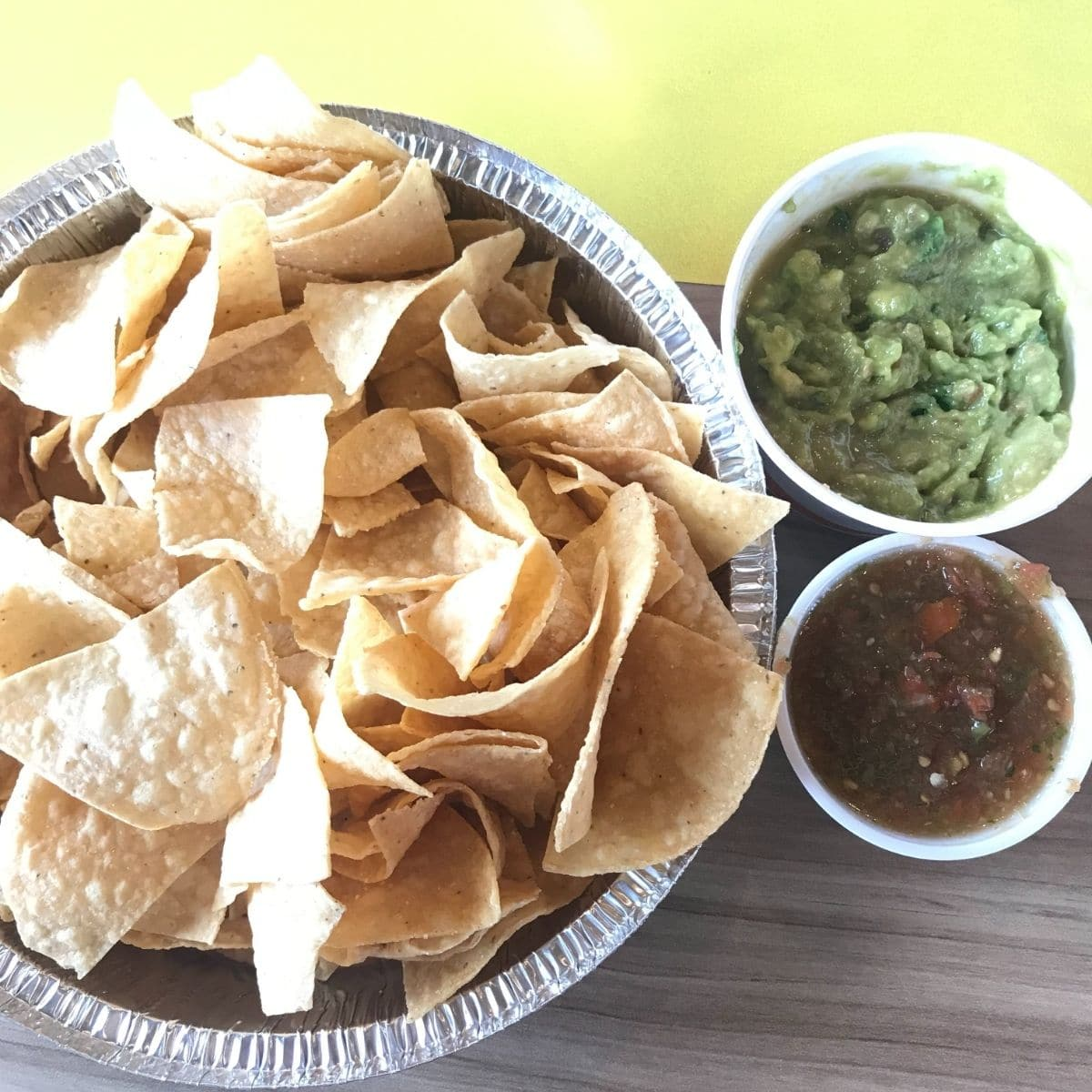 costa vida chips, guacamole, and salsa on a table that is wood and yellow