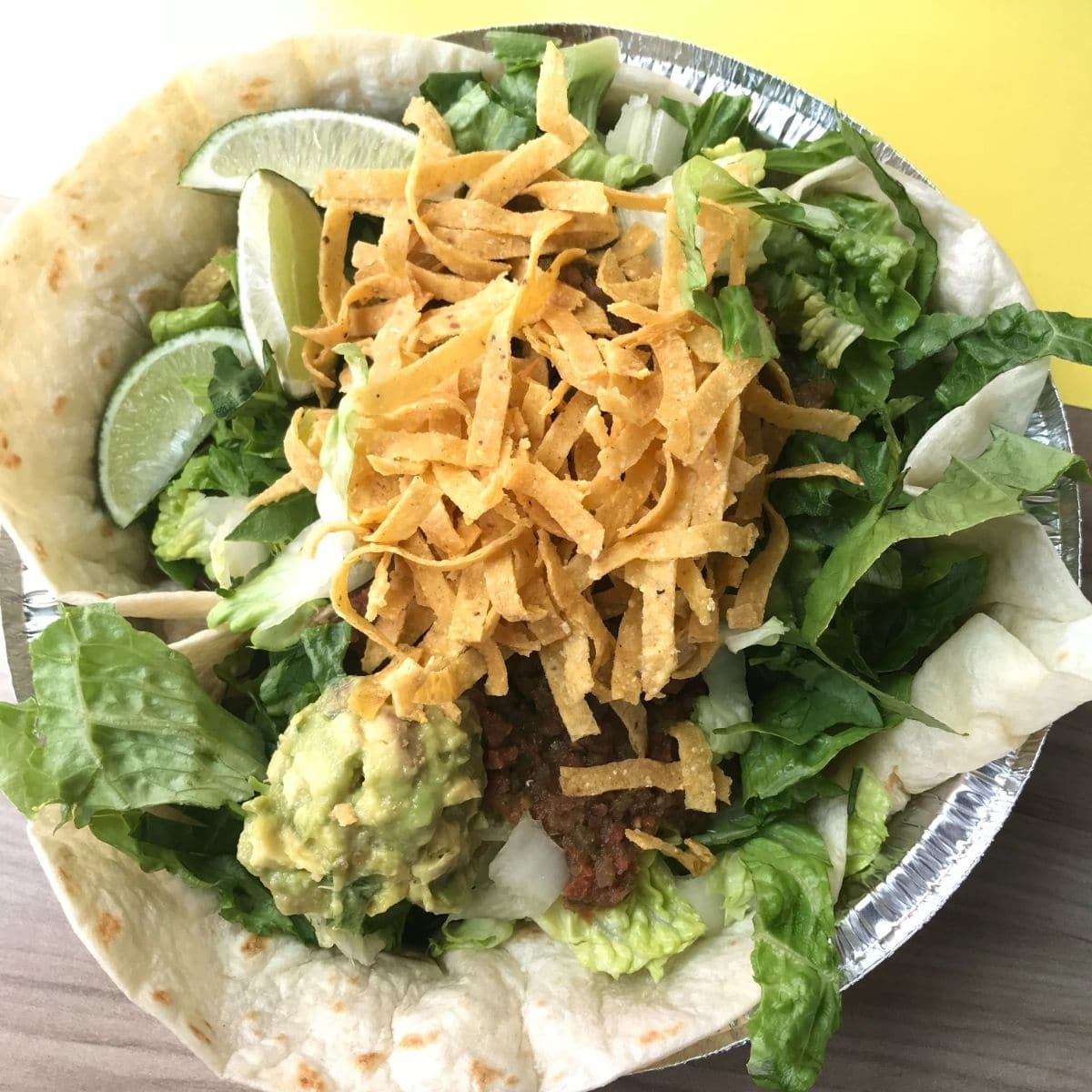 costa vida's veggie salad with a tortilla, lettuce, guacamole, chip strips, salsa, and limes with a wood and yellow background