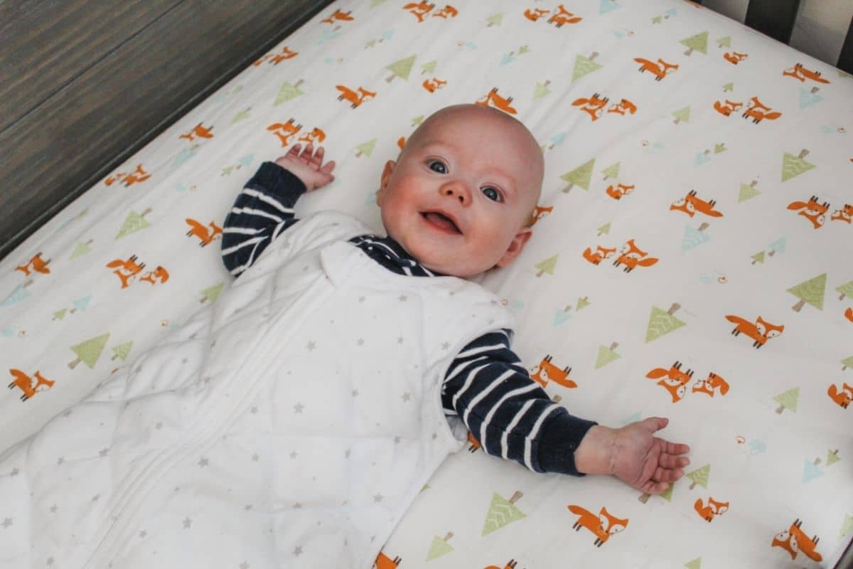 baby boy wearing the dreamland baby weighted sleep sack and laying on a sheet with foxes on it