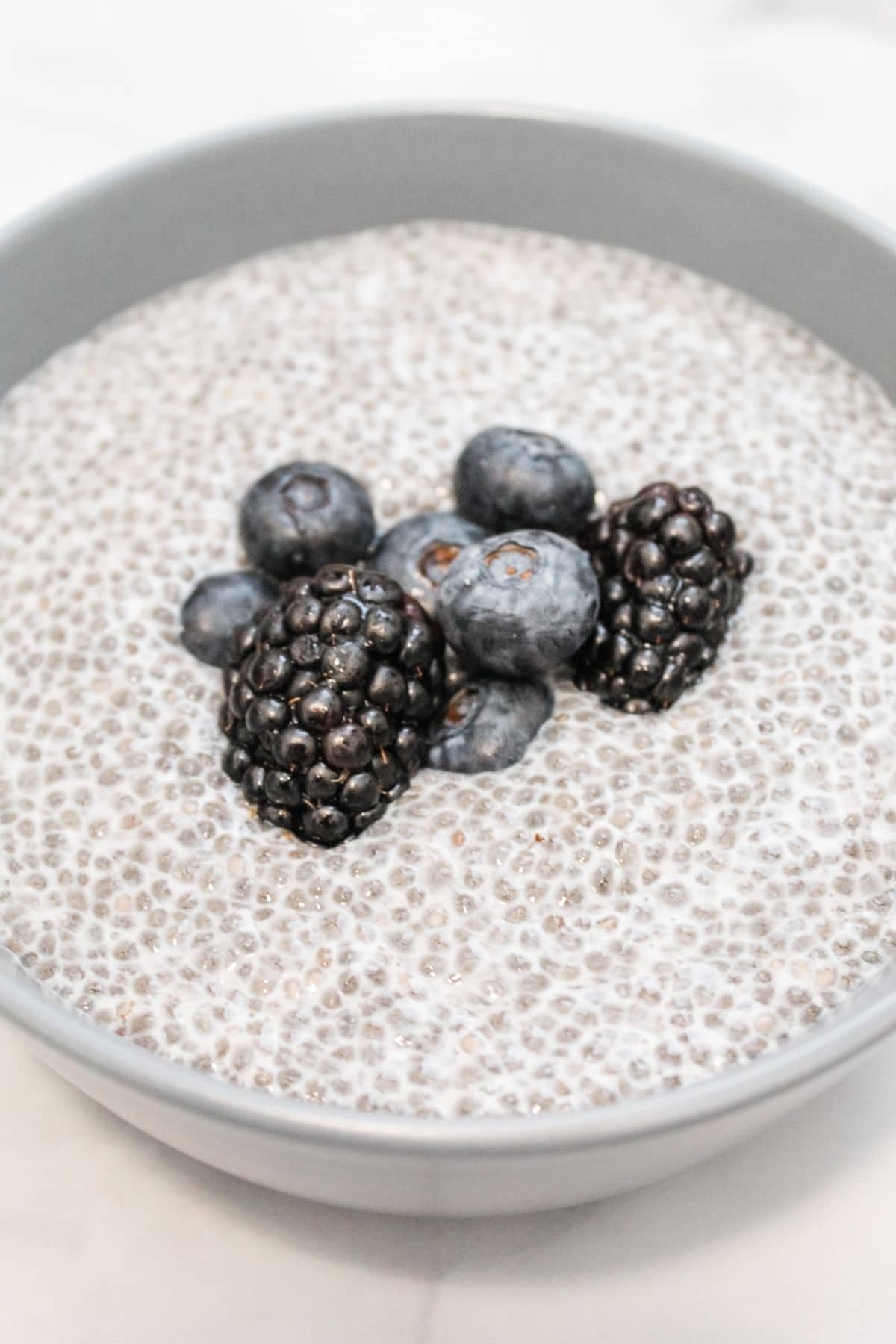 chia seed pudding mixture in a blue bowl on a white marble background