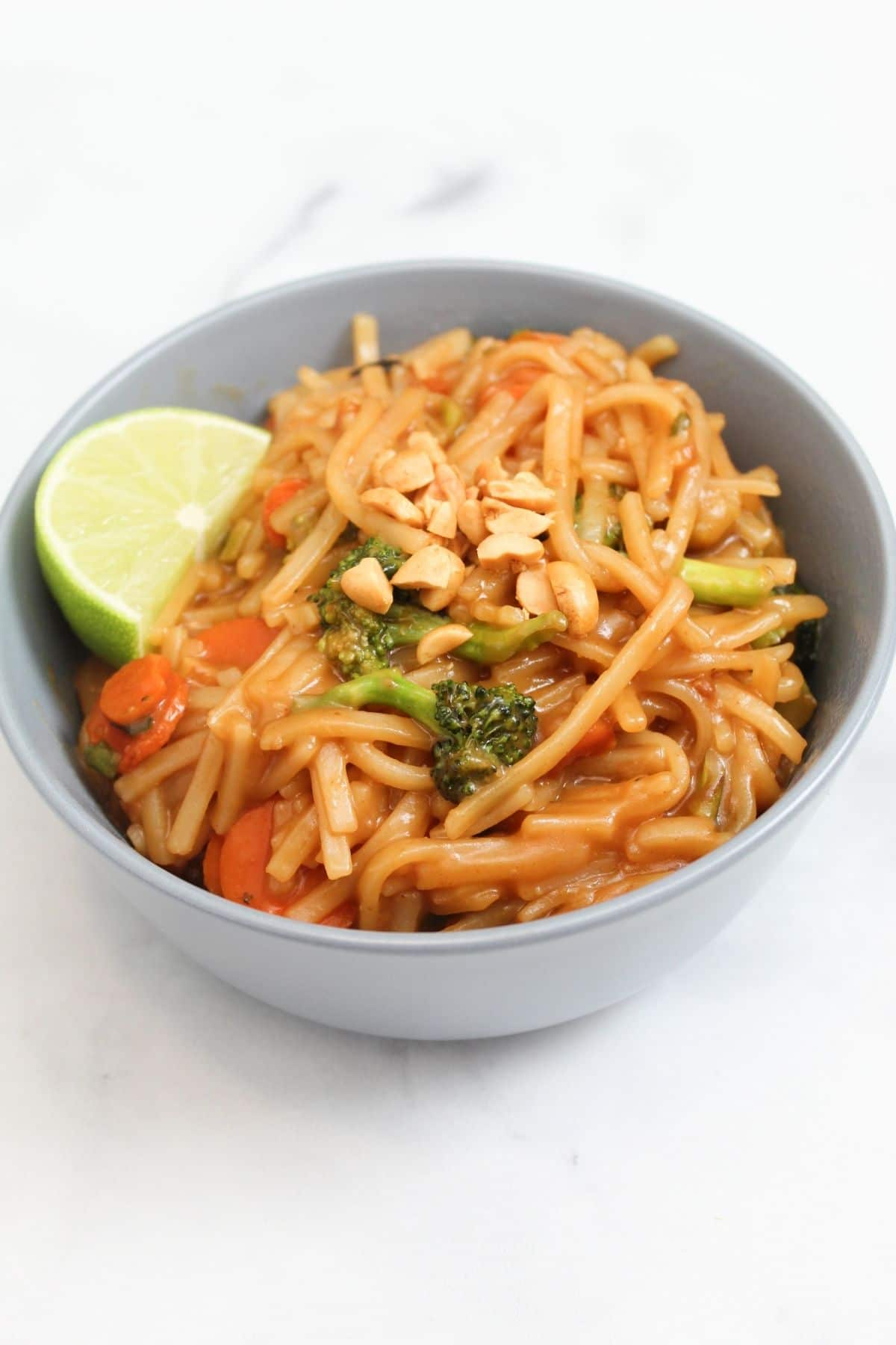 finished pad thai meal topped with chopped peanuts lime