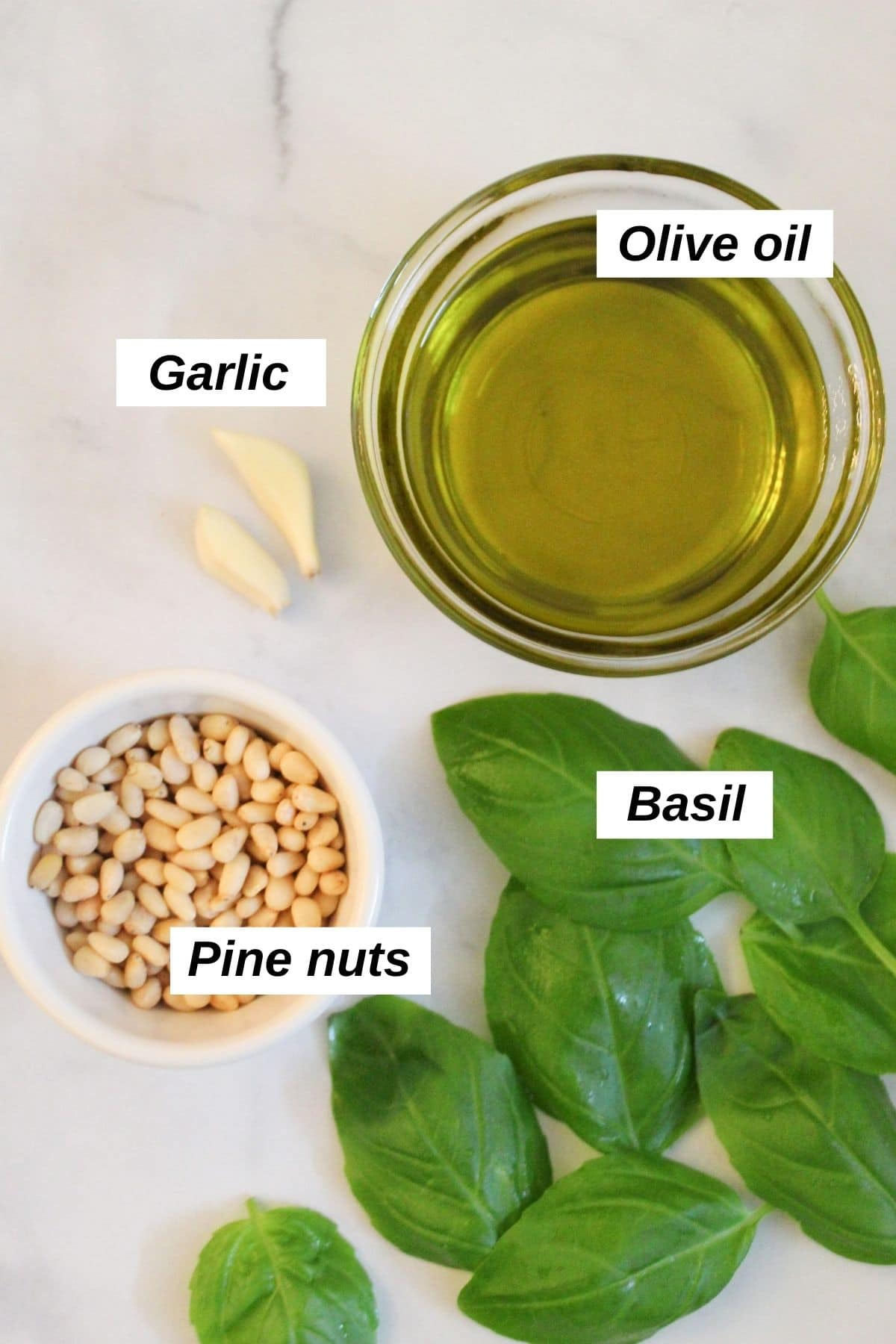 individual ingredients for vegan pesto sauce recipe on a white marble background