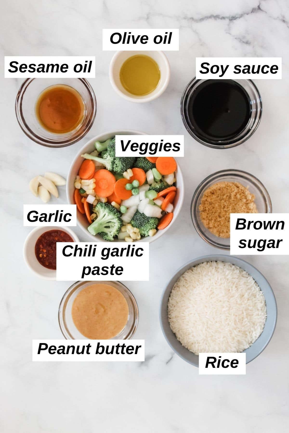 individual ingredients for vegan fried rice recipe in bowls on a white marble background