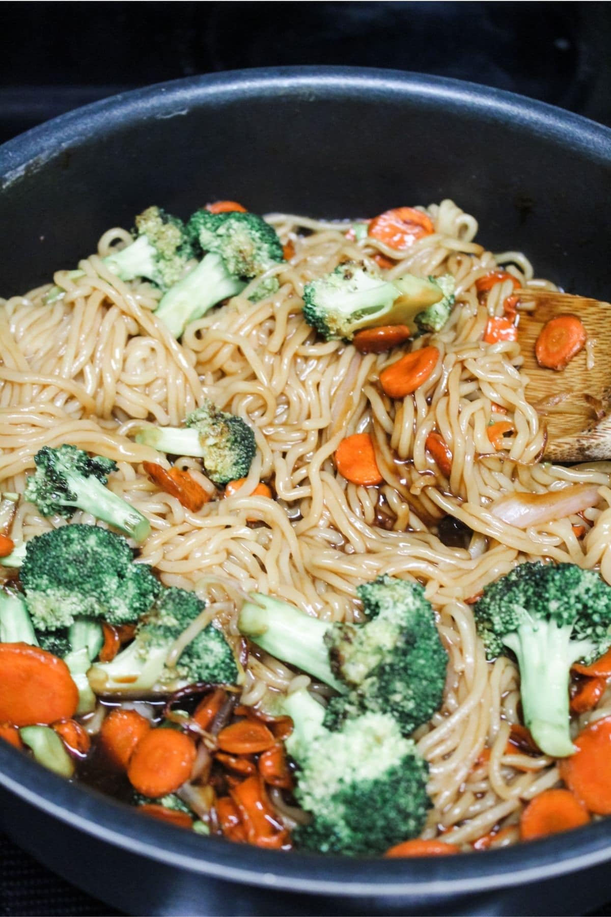 mixing together ramen noodles, broccoli, carrots, shallots, and Asian sauces over medium heat in a large pan