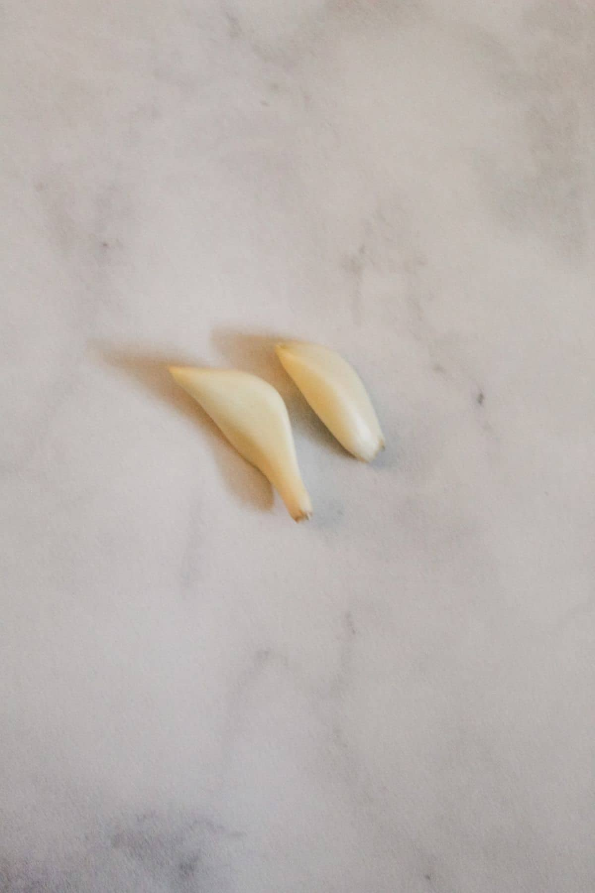 two cloves of garlic that have been peeled