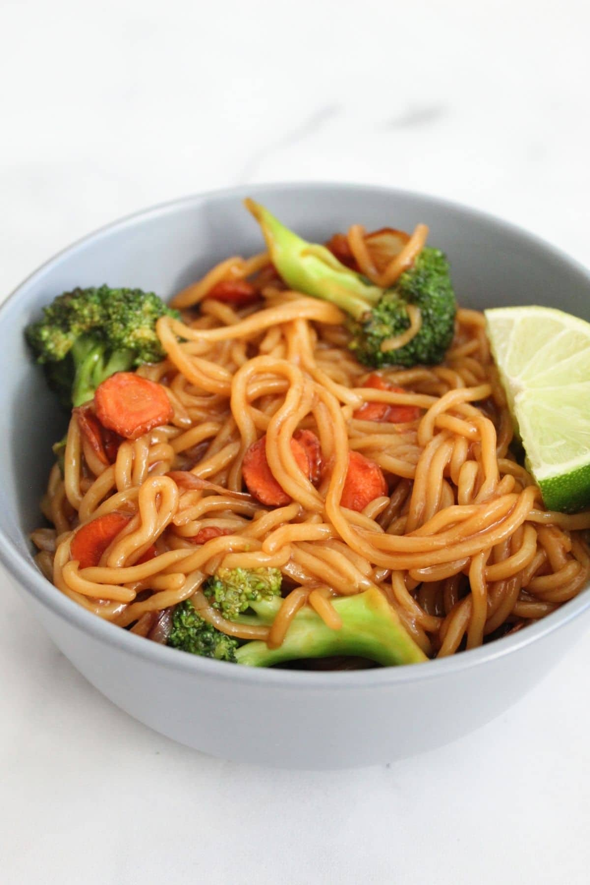 ramen noodle recipe with ramen noodles, veggies, and a lime wedge in a blue bowl on white marble