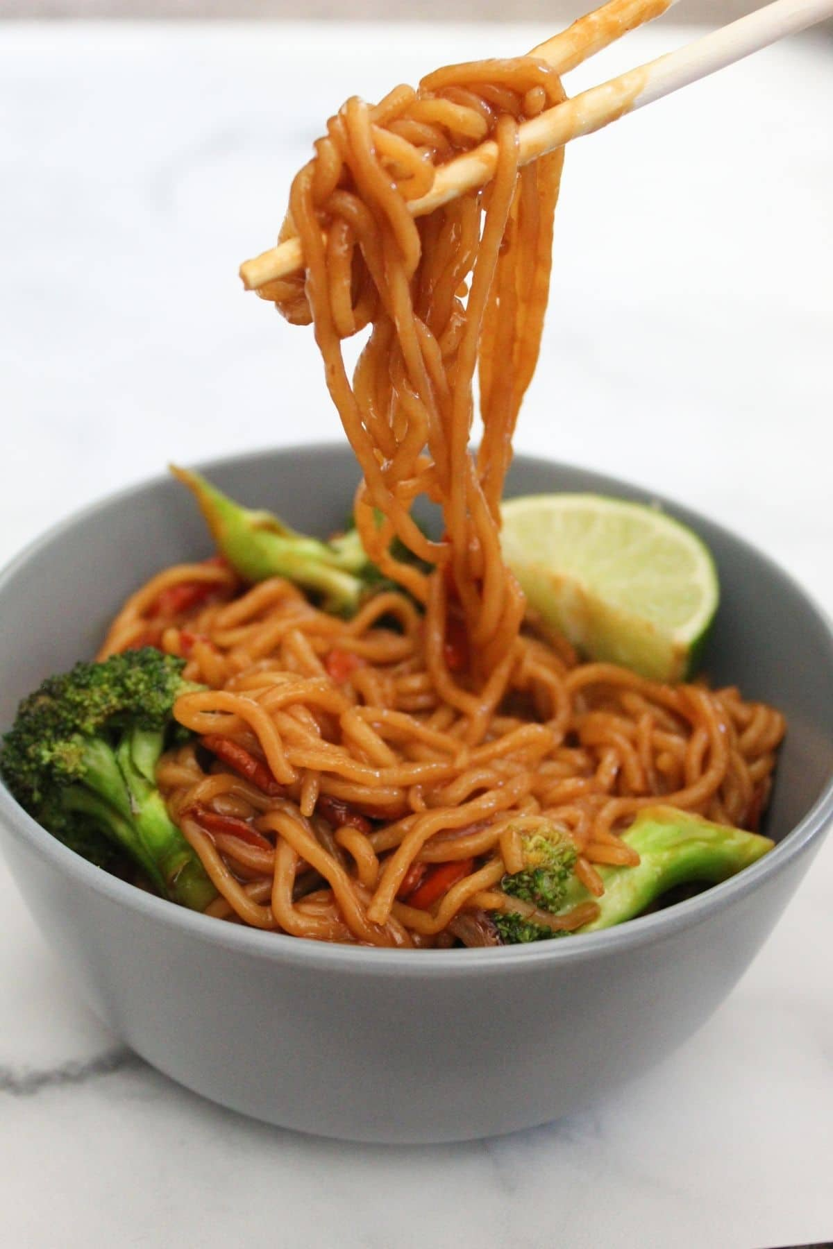 pulling up ramen noodle stir fry with veggies out of a bowl with chopsticks