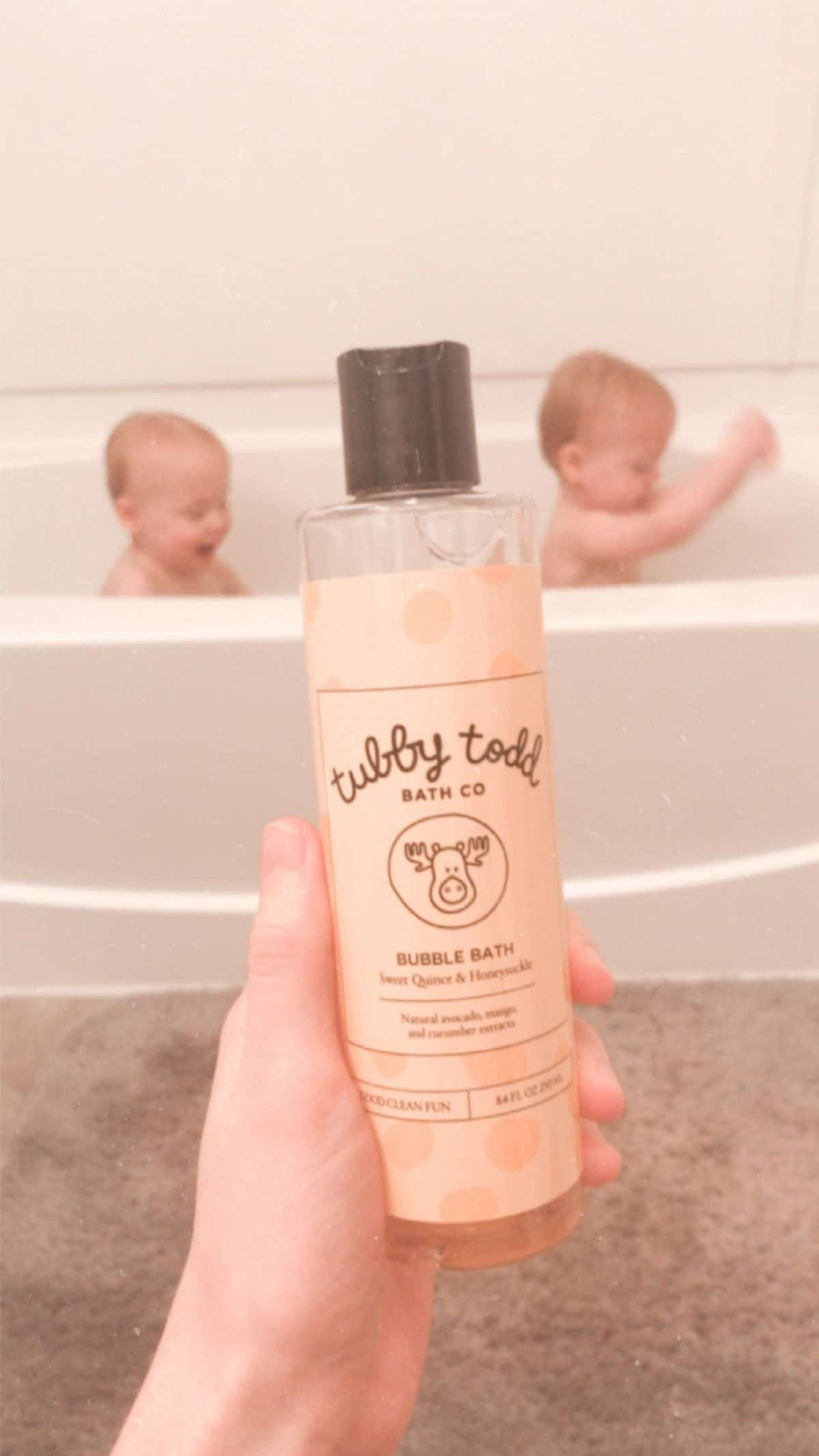 tubby todd bubble bath being held up in front of twin babies in the bath tub in the background