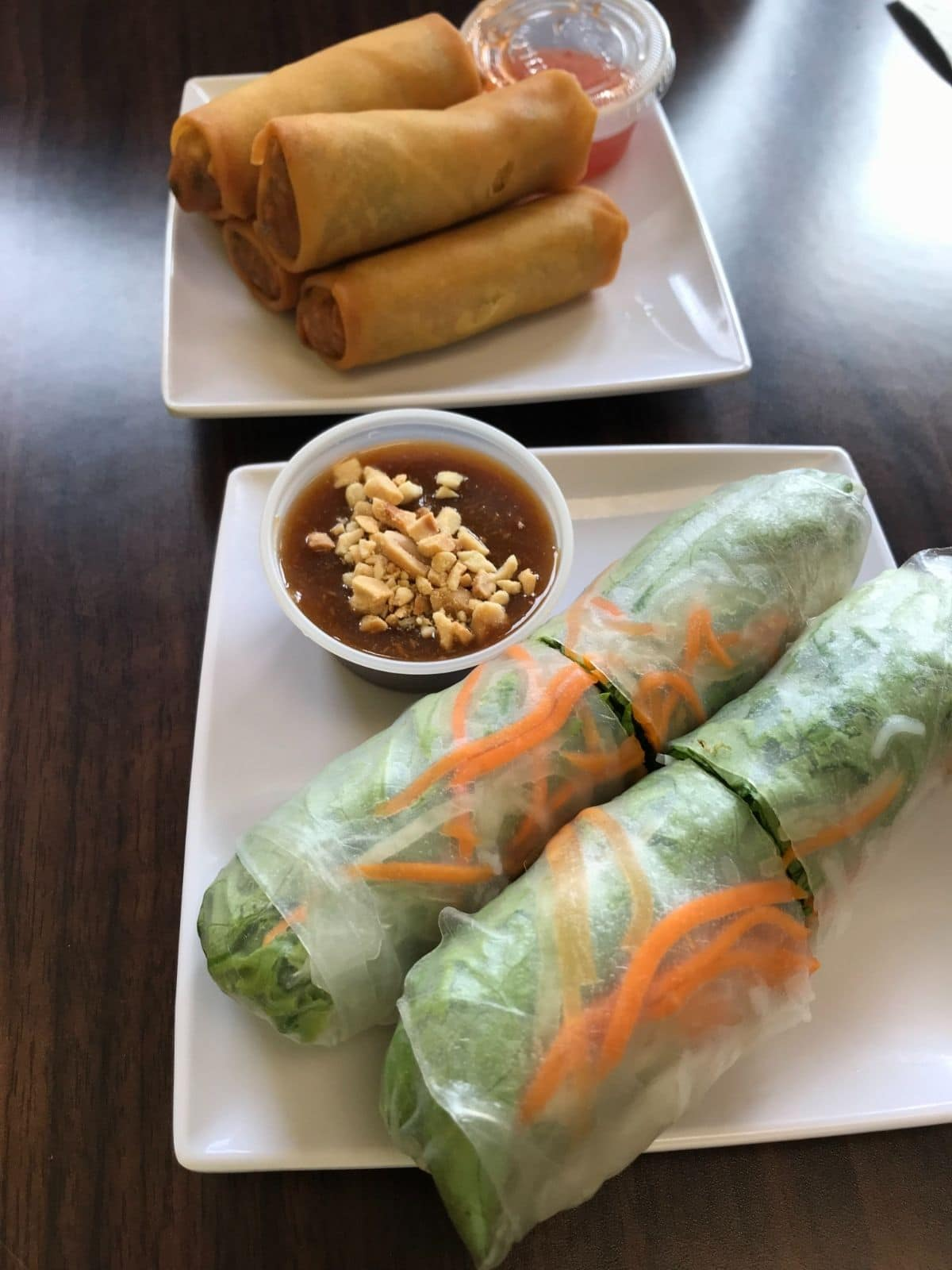 fresh spring rolls with a peanut sauce on a little white square plate and vegan egg rolls on a white square plate with a red sauce