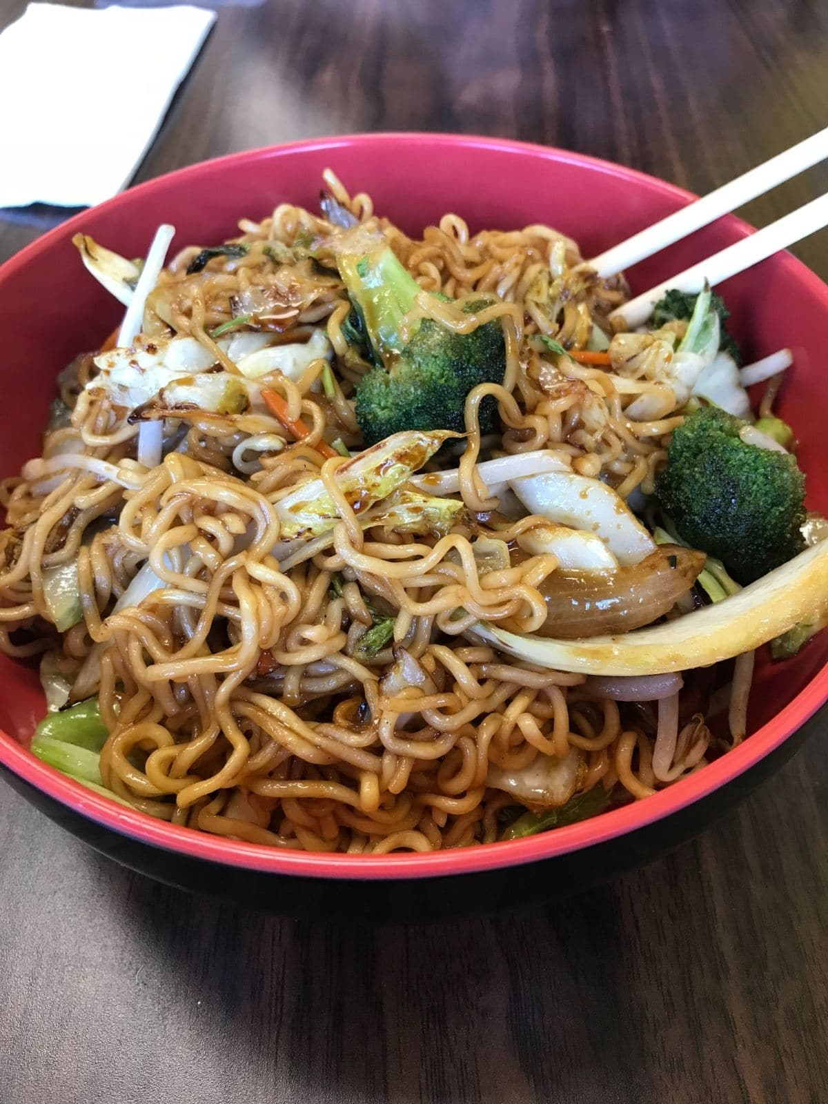 a red bowl with ramen noodles, broccoli, cabbage, onions, carrots, and chopsticks