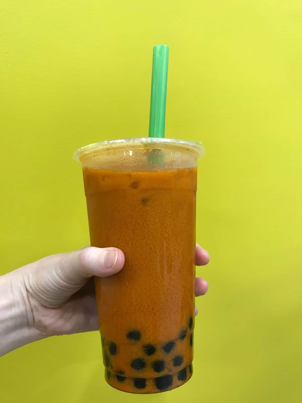 thai tea with boba being held up in a clear cup with a green straw against a yellow background