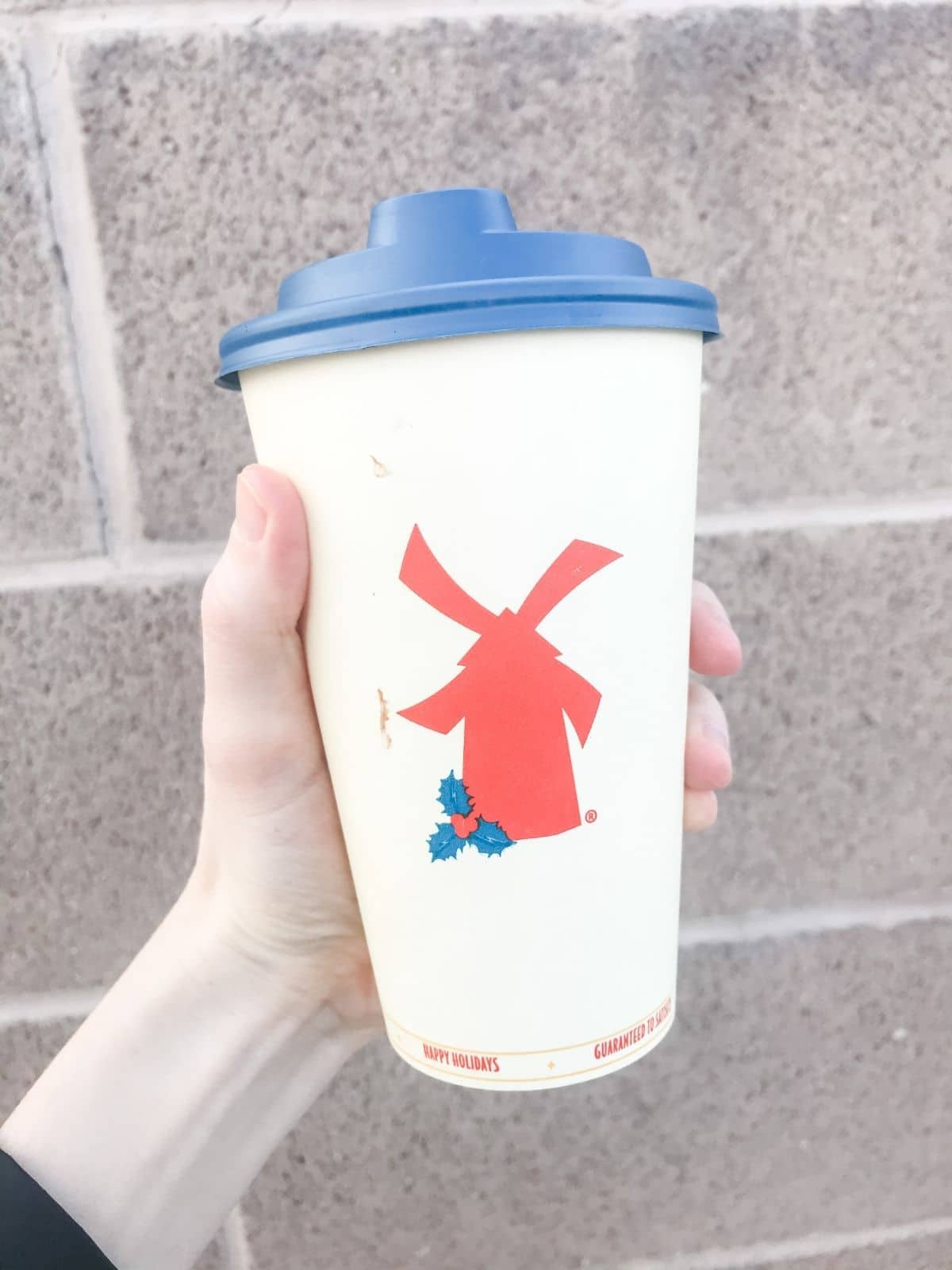 dutch bros vegan hot mocha with oat milk, chocolate, and salted caramel against a brick background