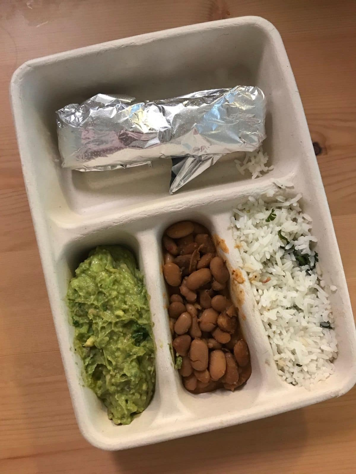 vegan kids meal from chipotle with a tortilla in foil, pinto beans, white rice, and guacamole on a wood table