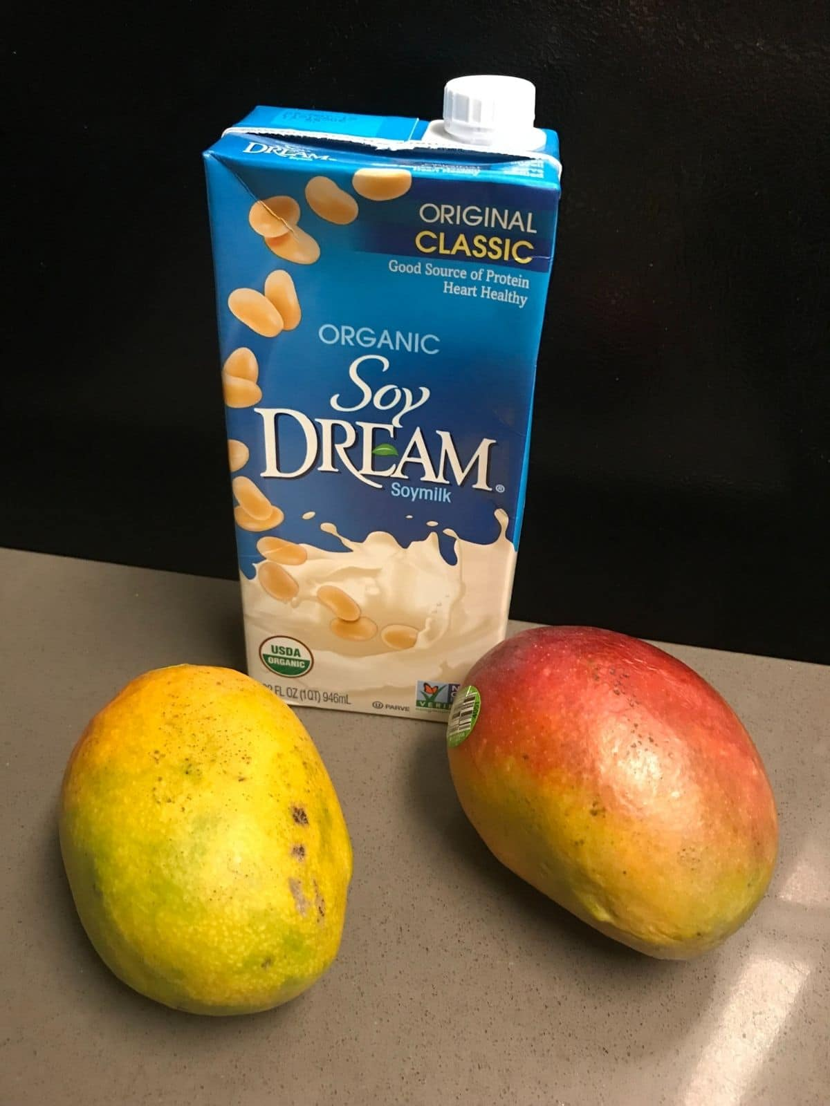 individual vegan mango smoothie ingredients that are soy milk and mangos on a grey counter