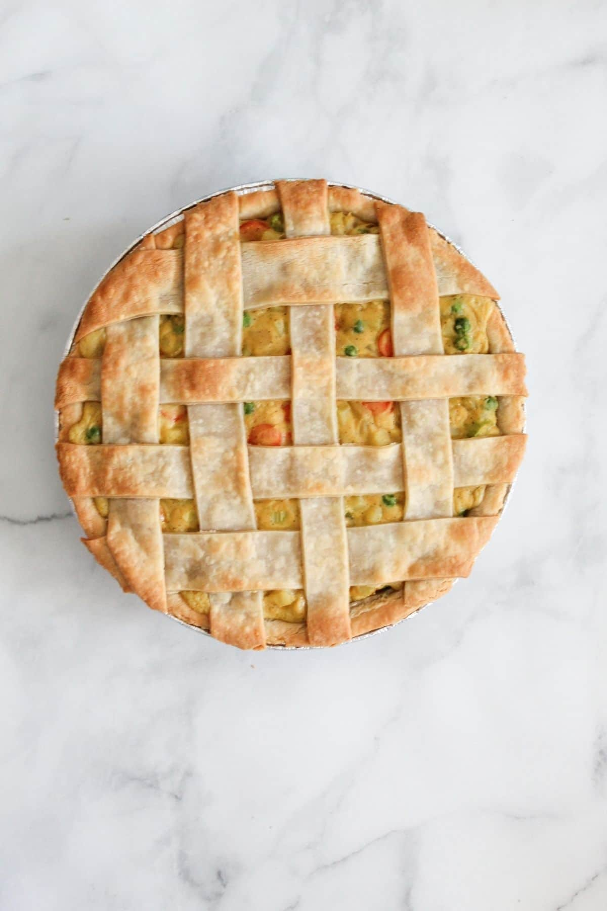 vegan pot pie in a pie tin from up above on a white marble background