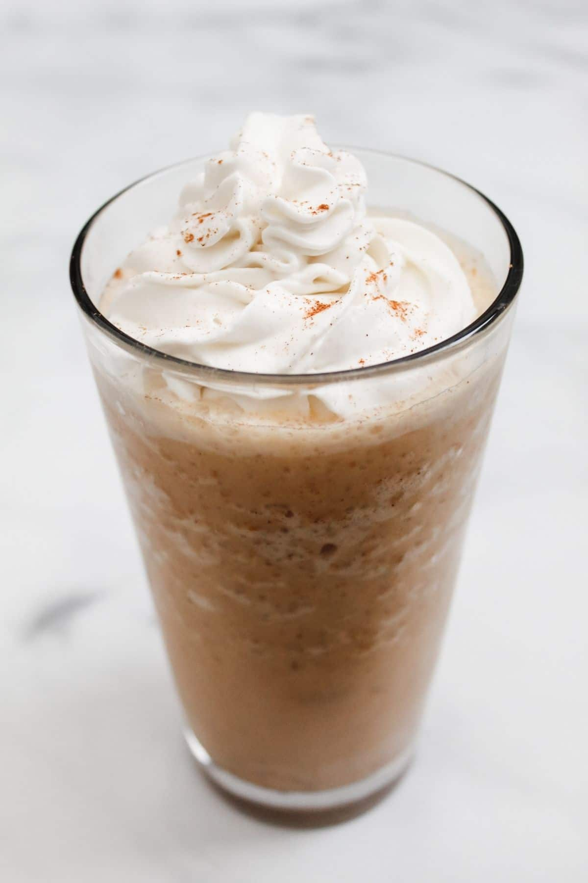 vegan pumpkin spice cream frappuccino with dairy free whipped cream in a glass with a white background