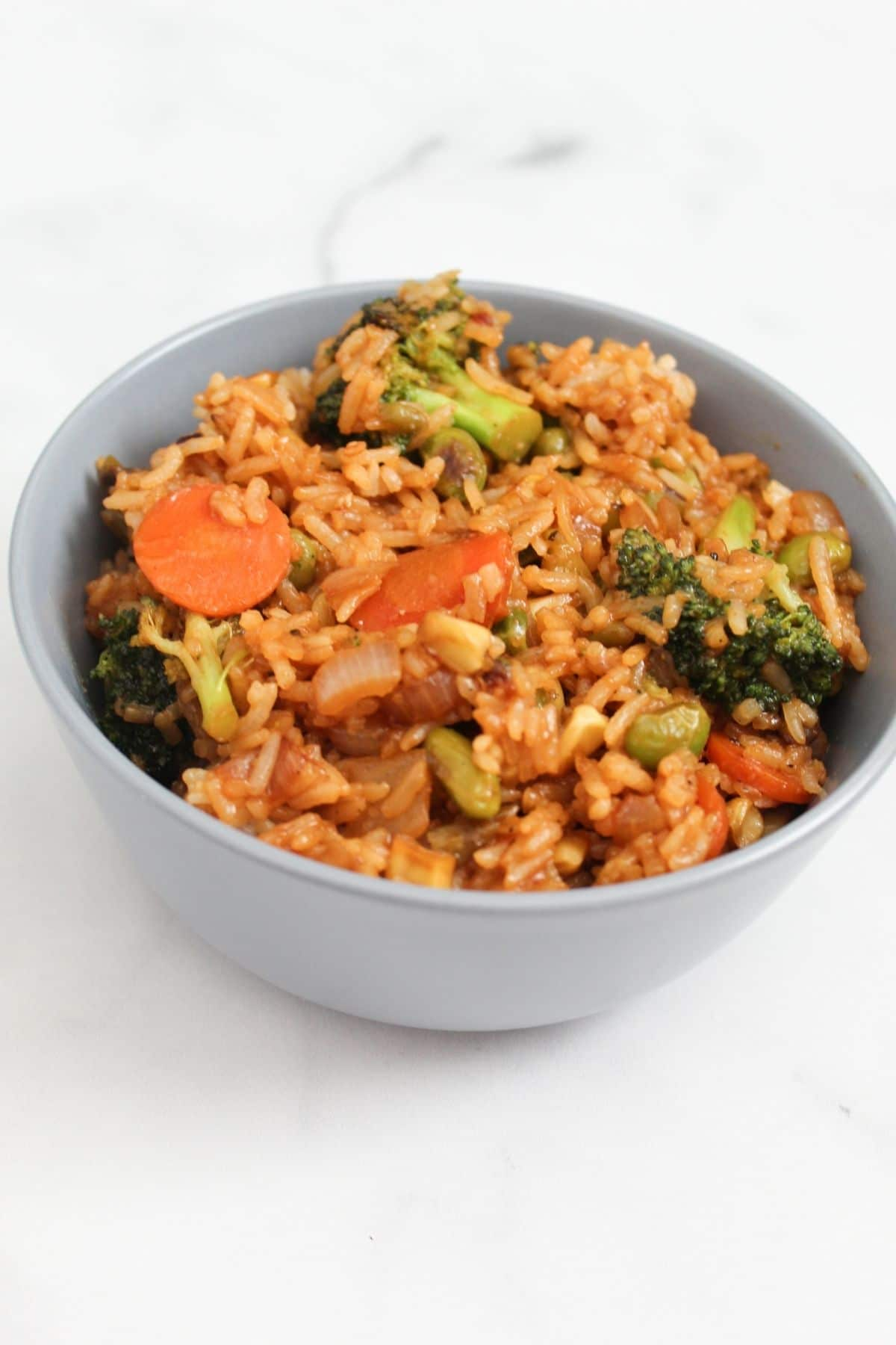 vegetable fried rice finished view on a blue bowl marble surface