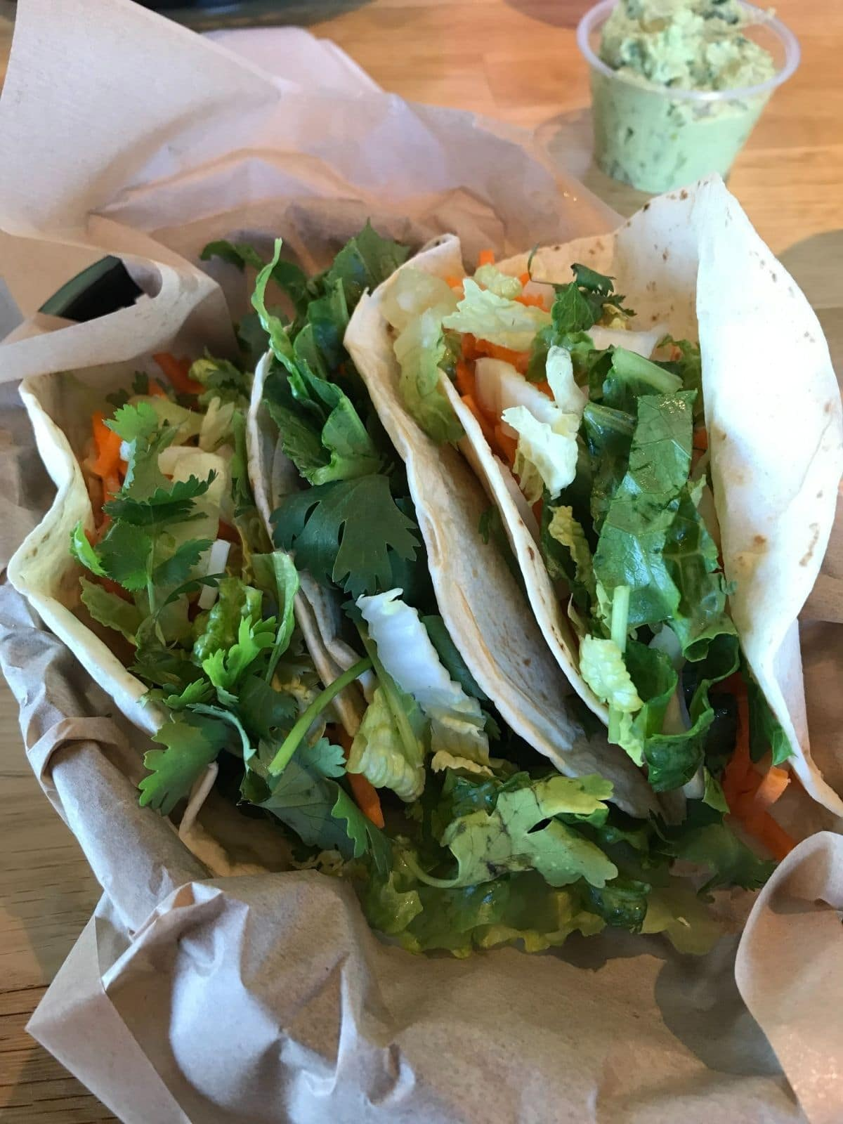 veggie tacos from zao asian cafe with lettuce, corn, carrots, cilantro, and tortillas with a cup of guacamole in the background