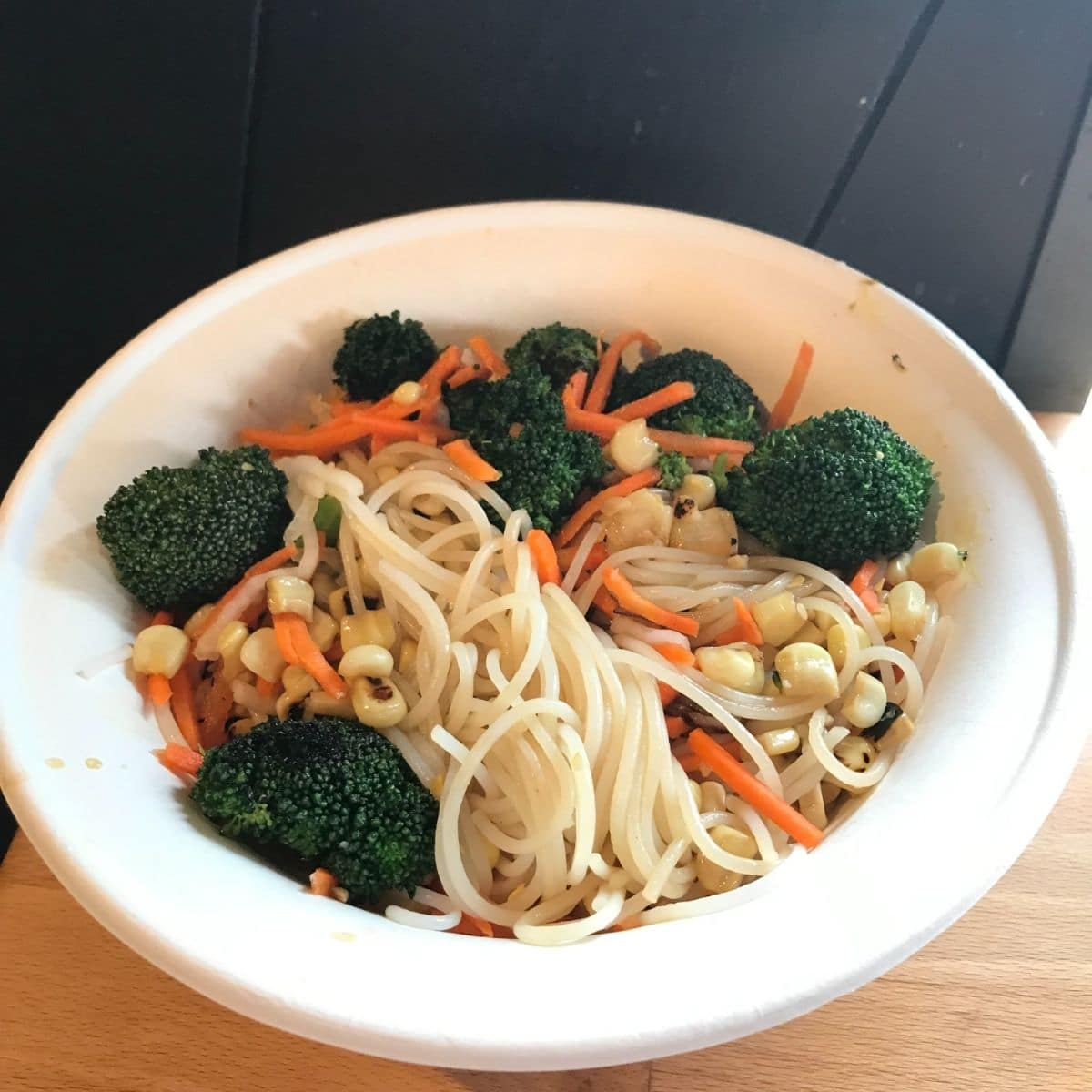zao asian cafe rice noodle bowl with corn, carrots, and broccoli in a white paper bowl on a wood table