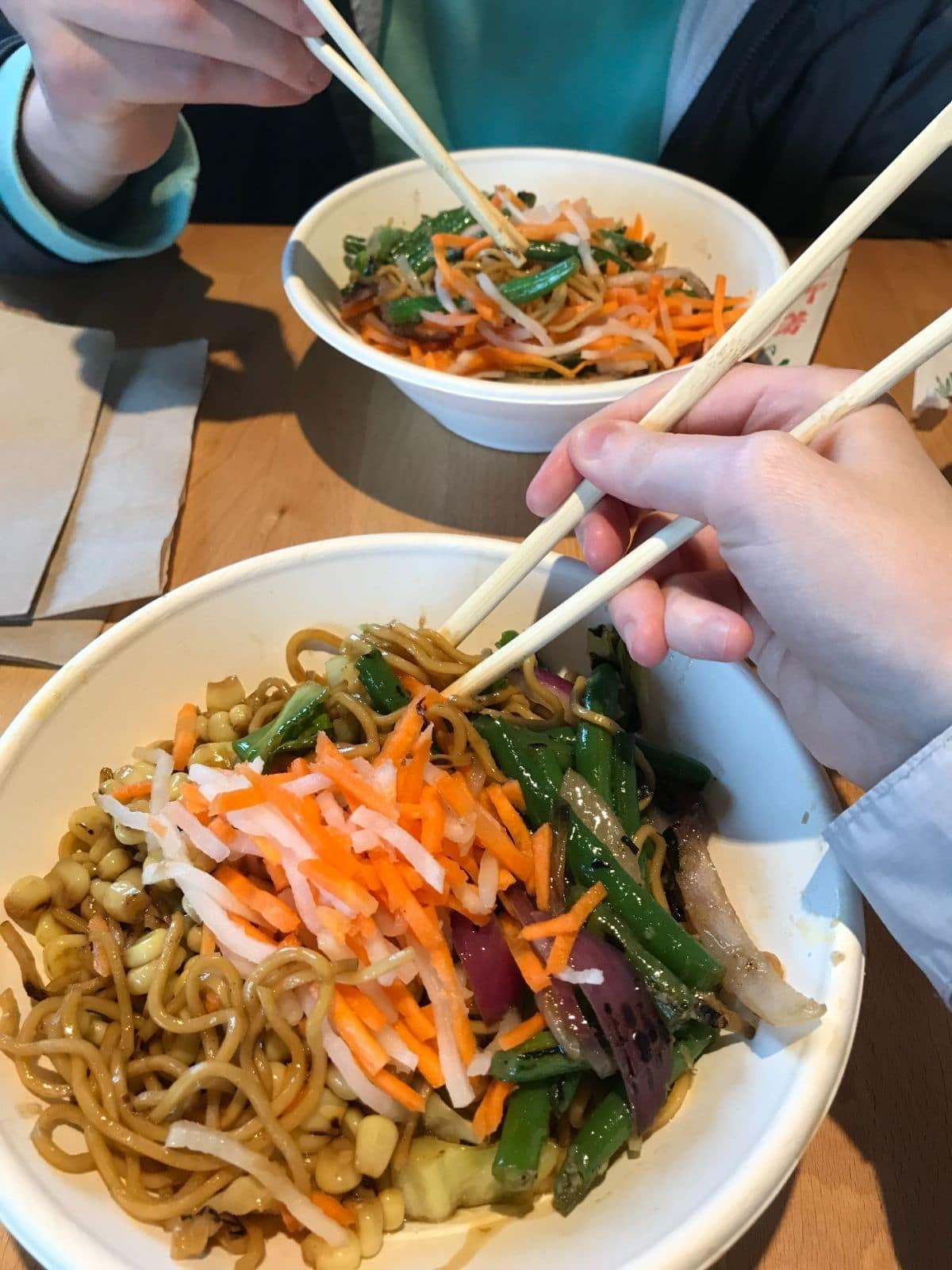 two bowls from zao that have yakisoba noodles, corn, green beans, carrots, and onions and are being eaten with chopsticks