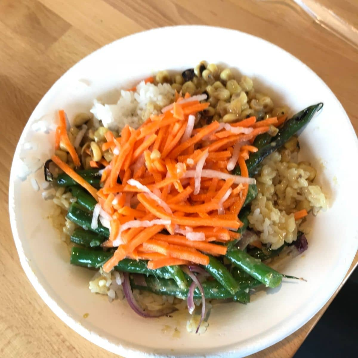 rice bowl with yellow curry, green beans, onions, carrots, and corn in a white paper bowl on a wooden table