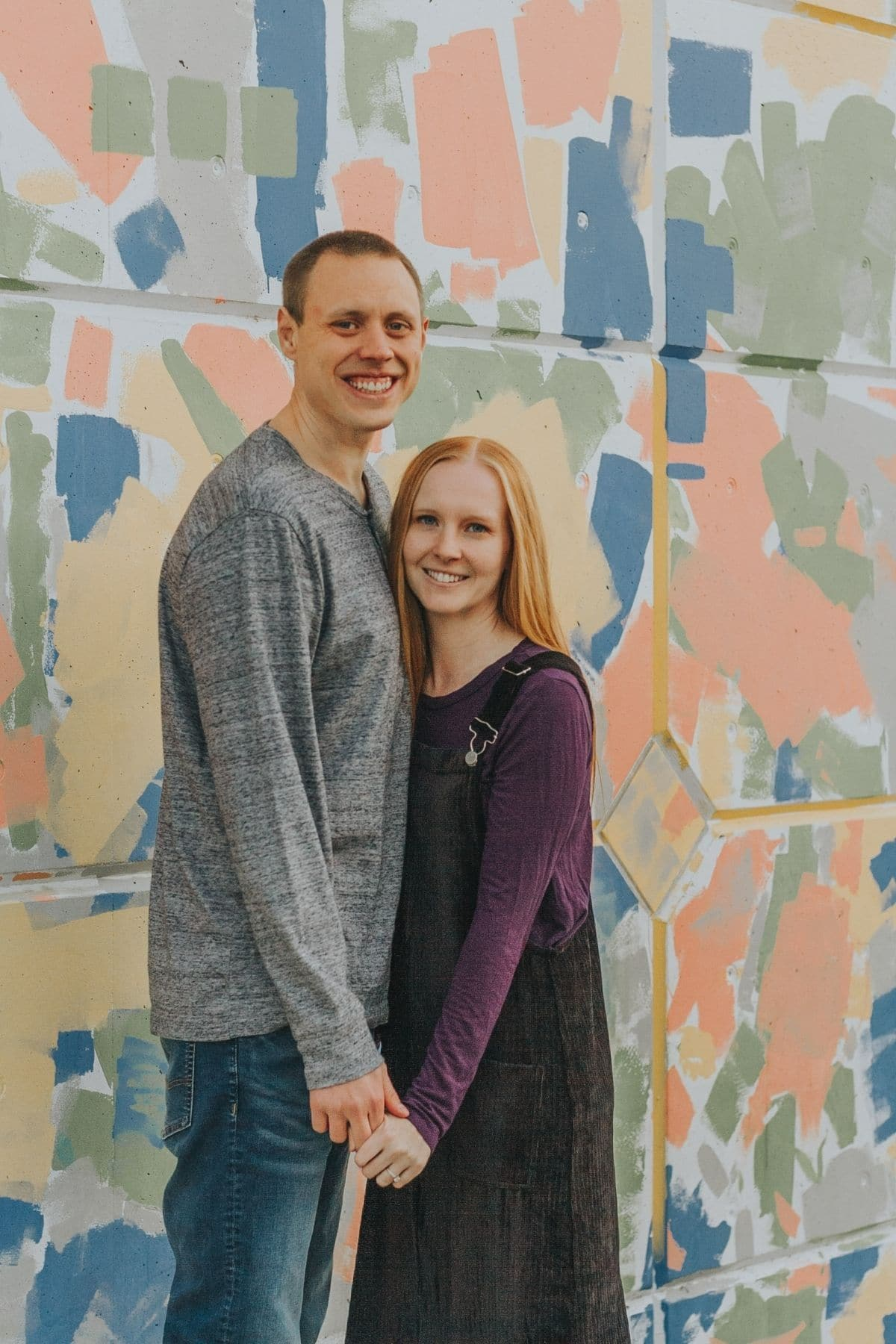Adam and Liz holding hands in front of abstract painted wall