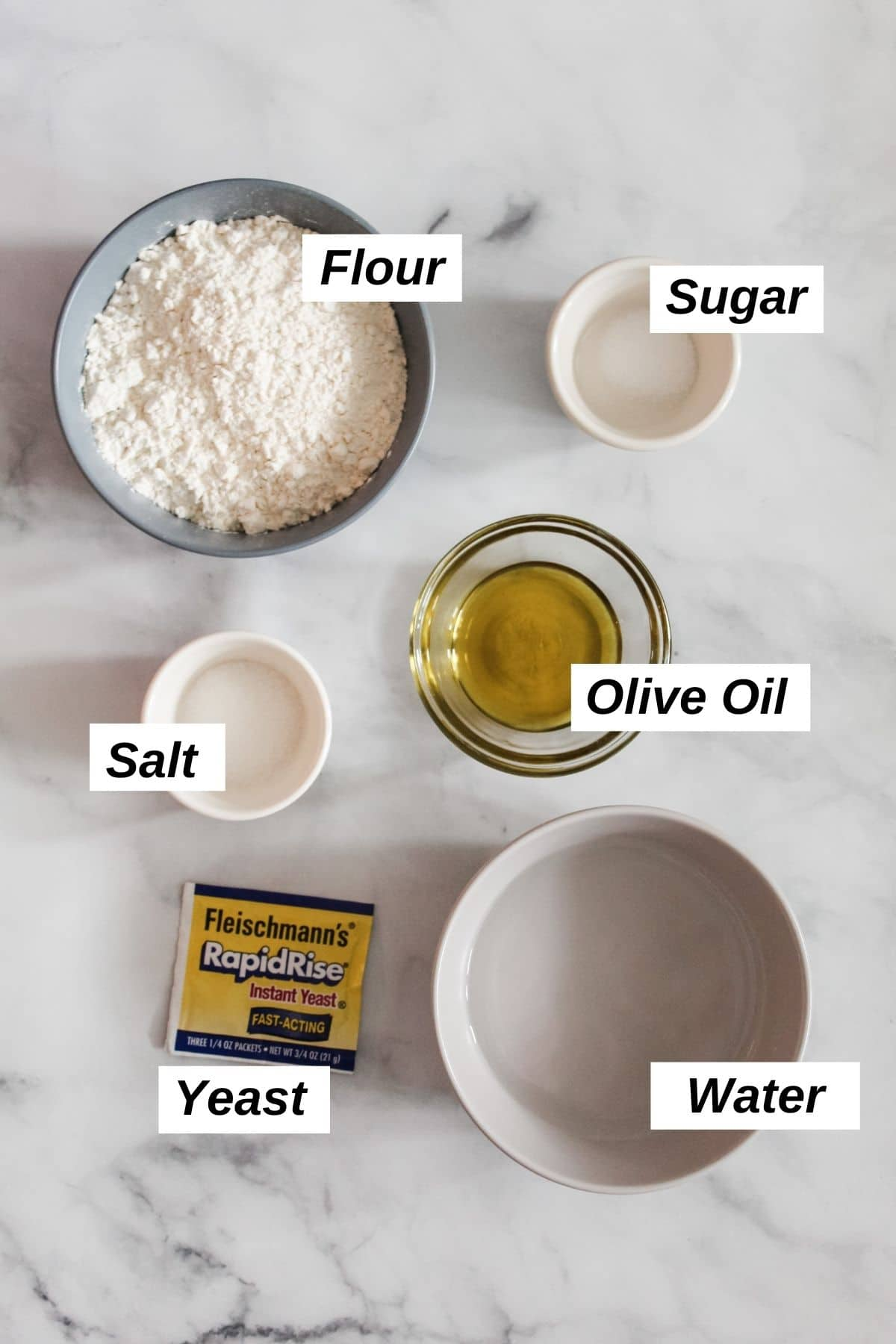 individual ingredients for pizza dough in little bowls including flour, sugar, salt, olive oil, water, and yeast