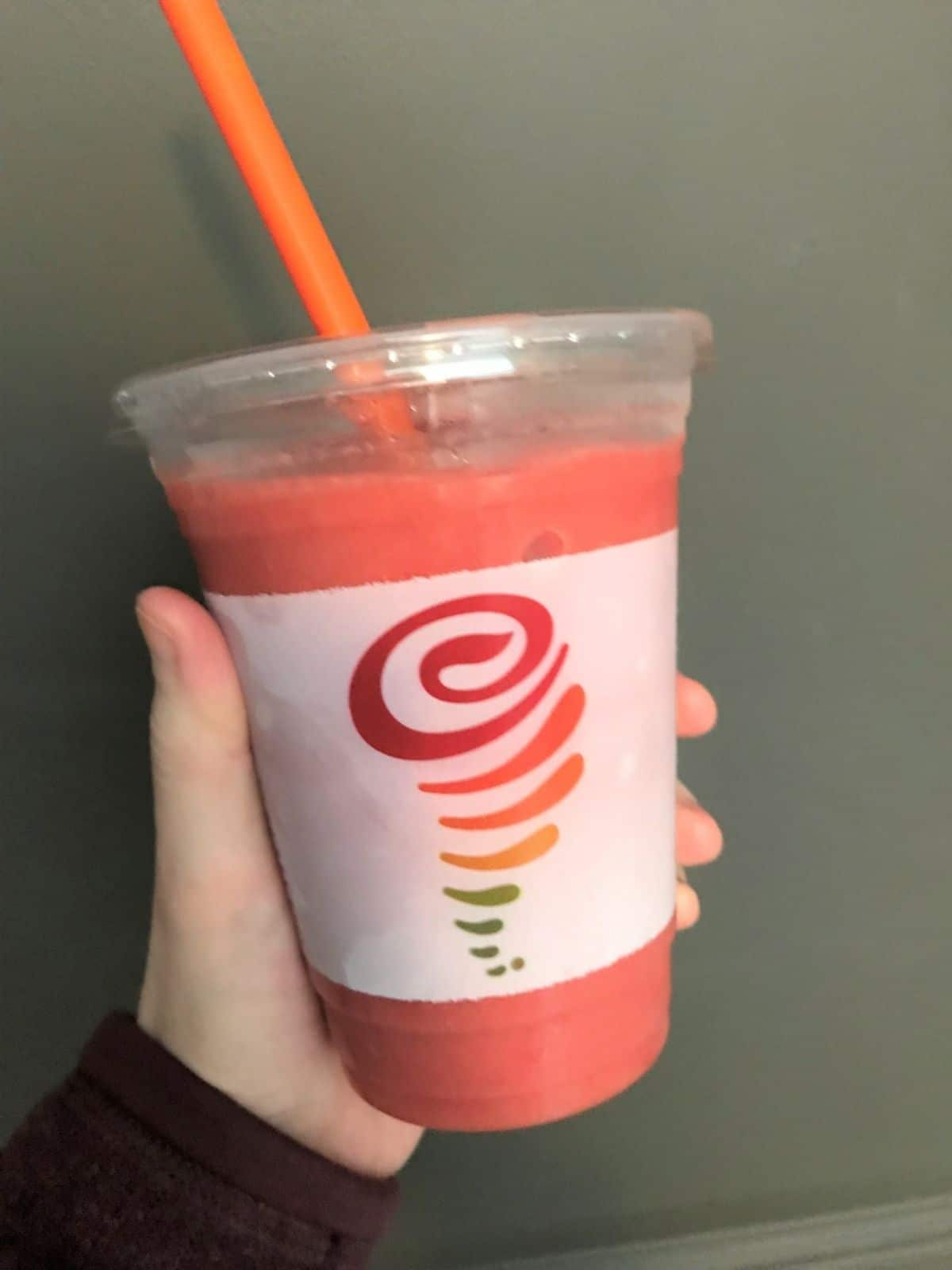 Pomegranate Paradise Smoothie from jamba juice in a clear cup with an orange straw being held in a hand