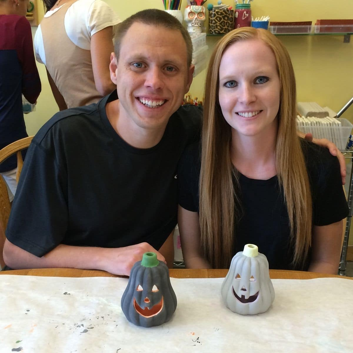 adam and liz at color me mine with their painted pumpkins