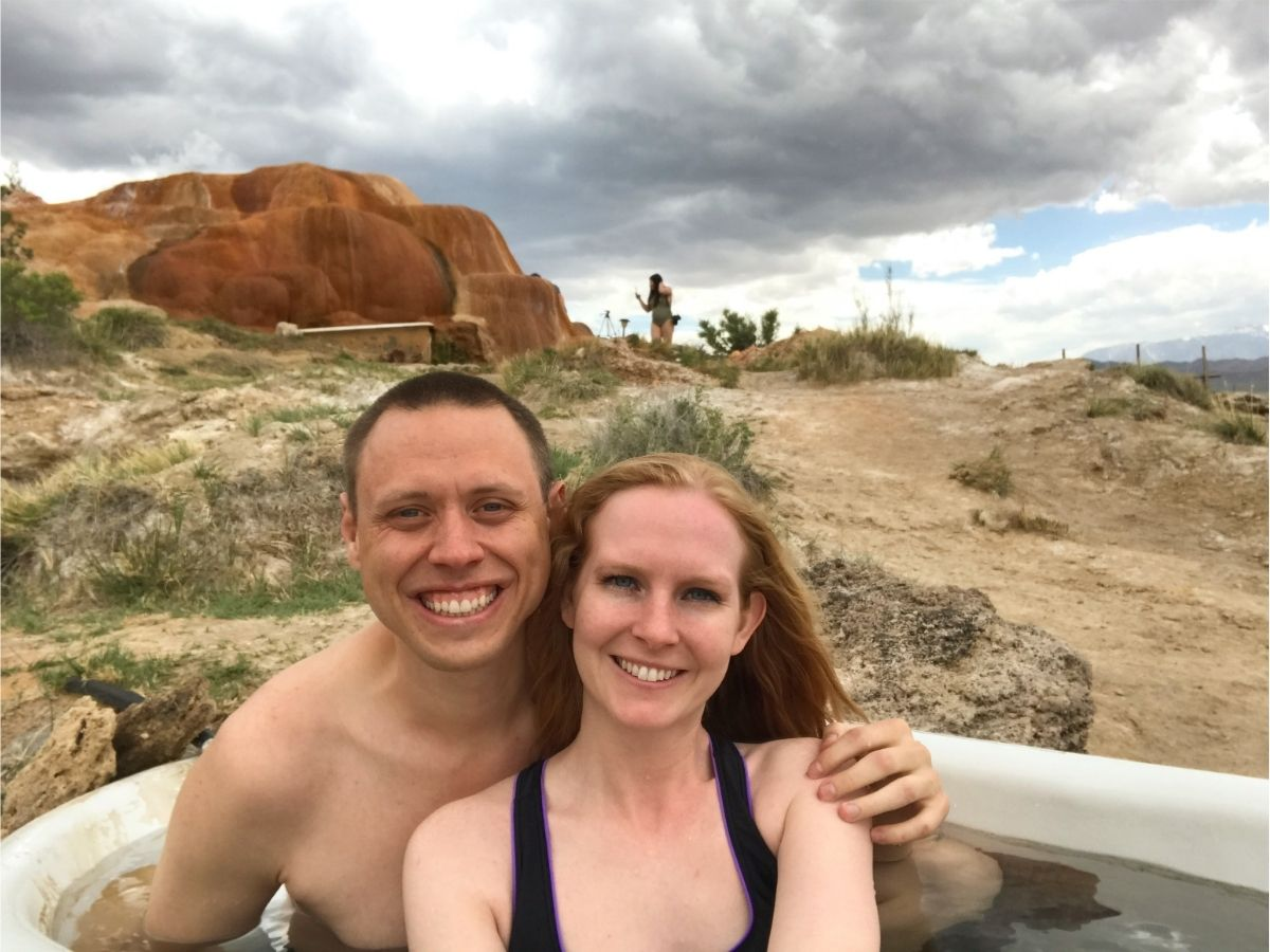 adam and liz sitting in a hot tub at mystic hot springs