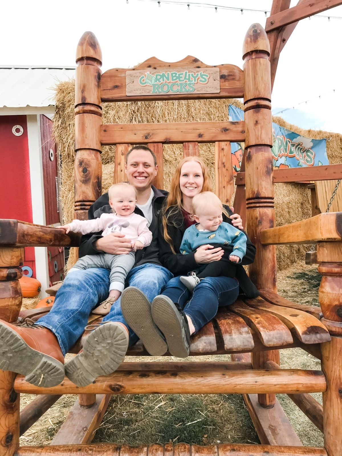 Adam and Liz and twins sitting in big wooden chair at Cornbelly's