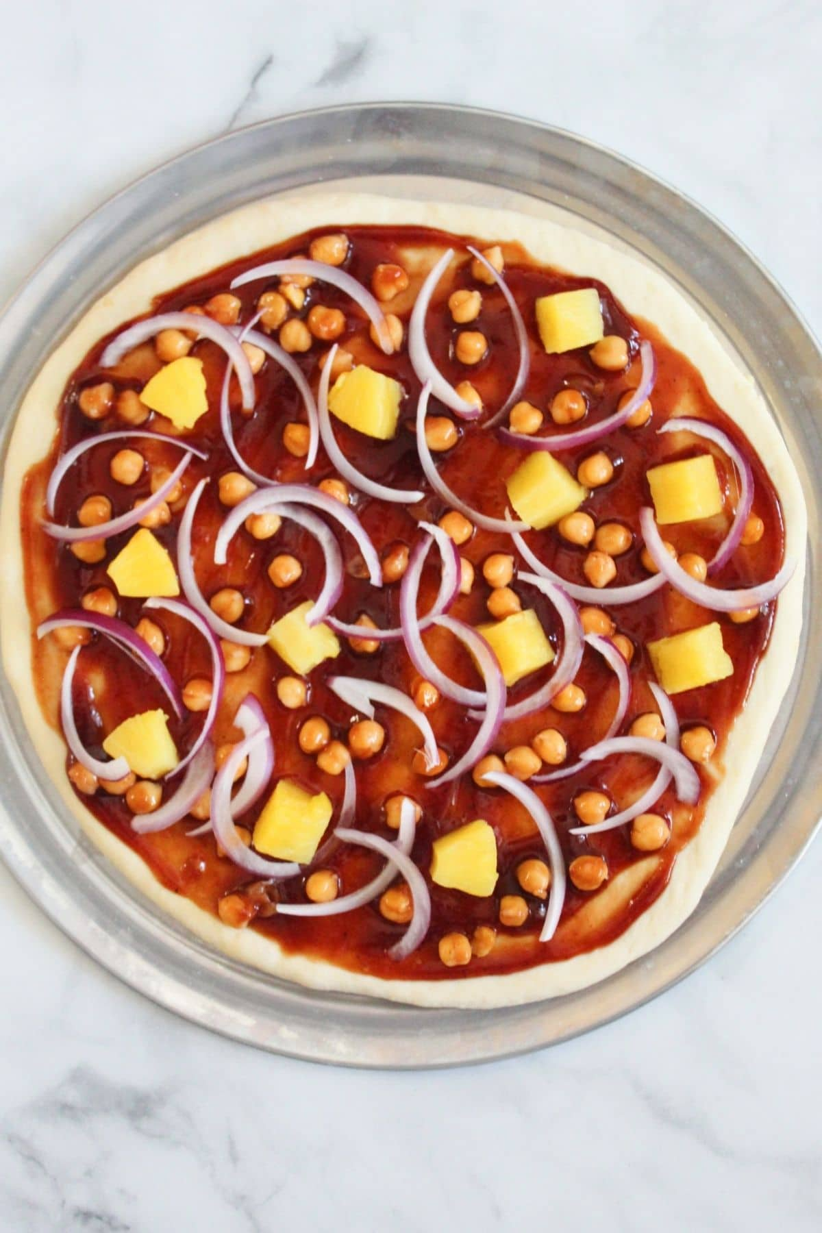 assembled pizza with bbq sauce, rolled out pizza, dough, chickpeas, pineapple, and red onions