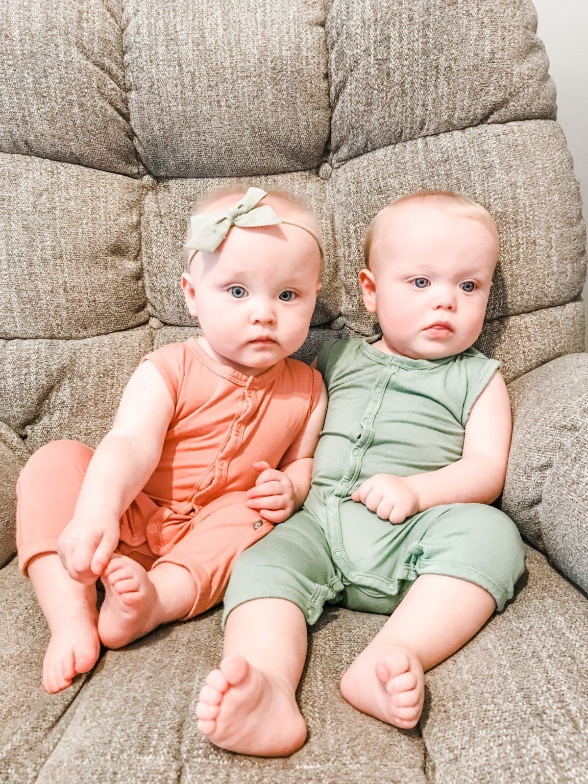 two babies sitting in a chair wearing matcha and terracotta kyte baby sleeveless rompers