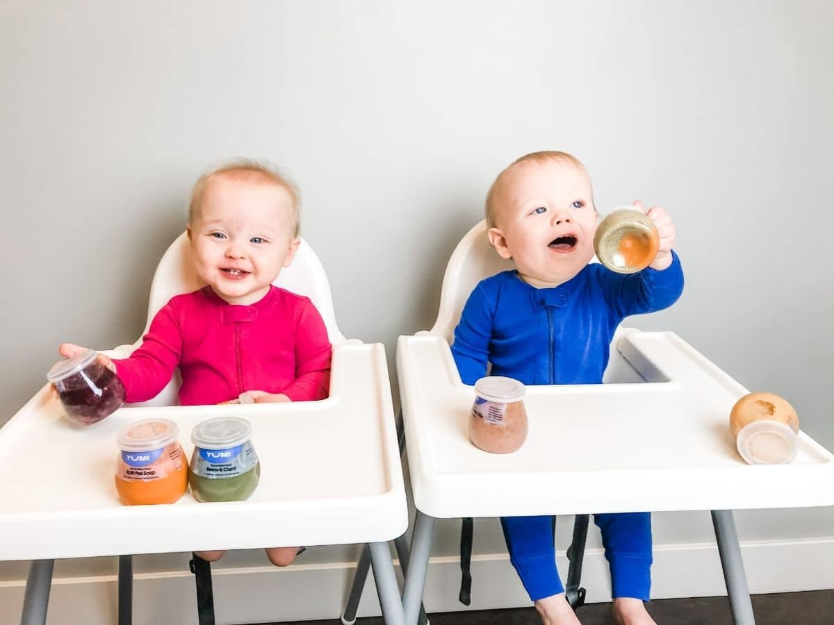 baby boy and baby girl in high chairs playing with yumi baby food jars