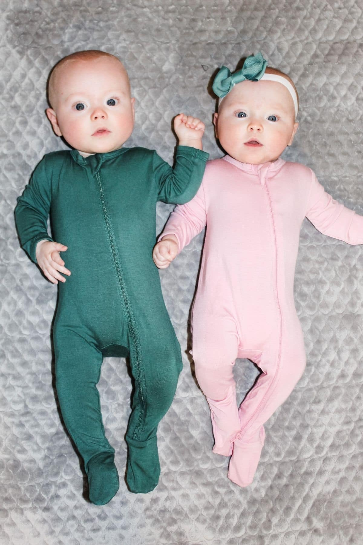 baby boy and baby girl wearing emerald and petal kyte baby bamboo pajamas and laying on a grey blanket