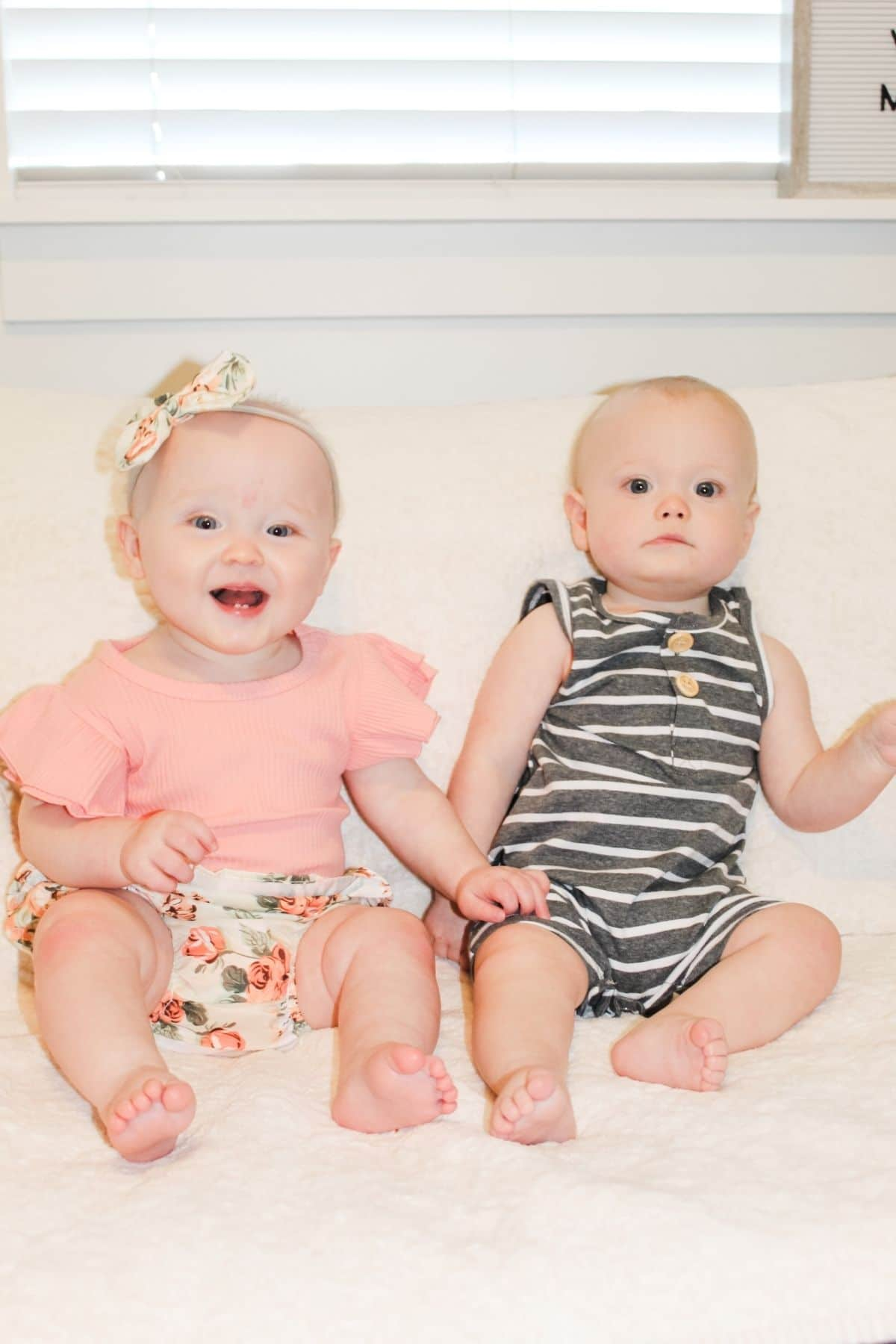 baby girl wearing pink floral outfit and boy wearing striped romper sitting up on a couch