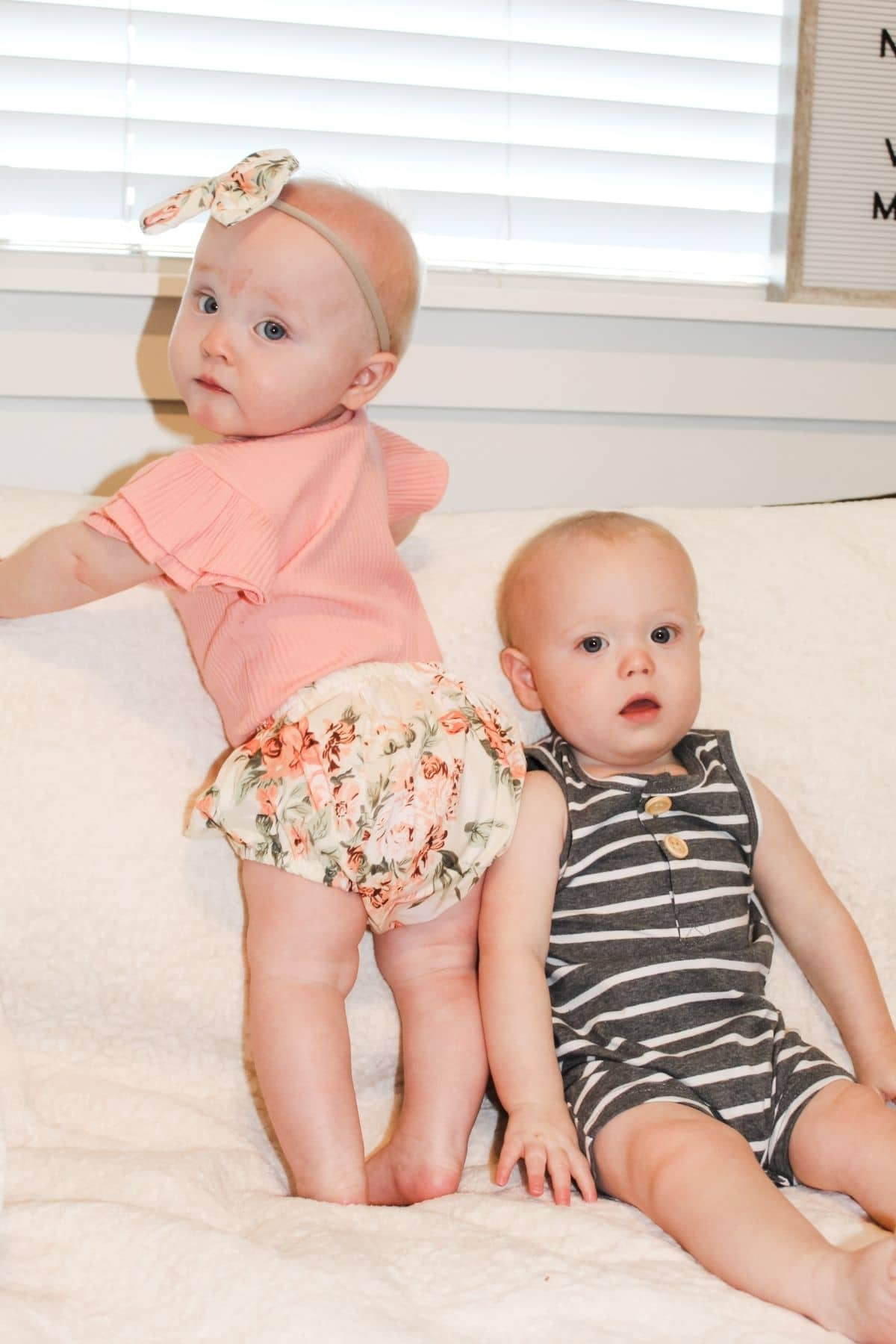 boy girl twins wearing eclair co baby clothes sitting next to each other on a couch