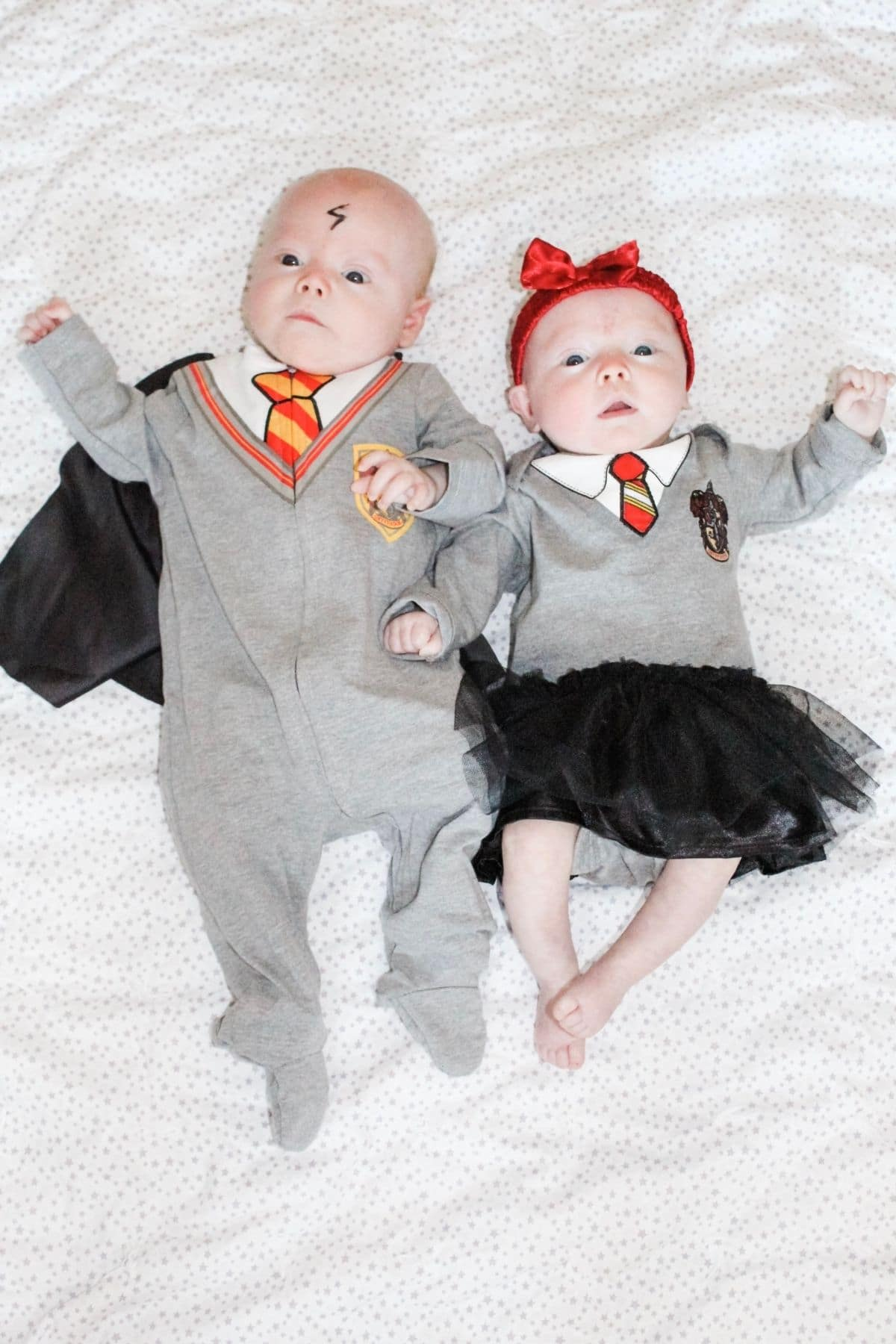 boy girl twin babies wearing harry potter halloween costumes laying on a white blanket