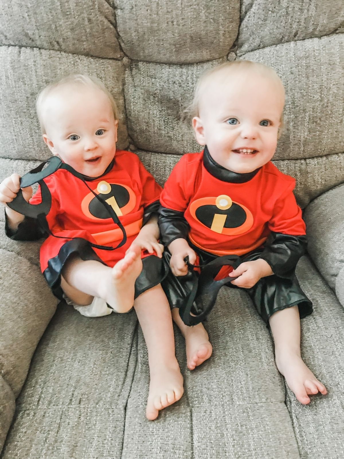 boy girl twin toddlers wearing incredibles halloween costumes and sitting in a grey chair