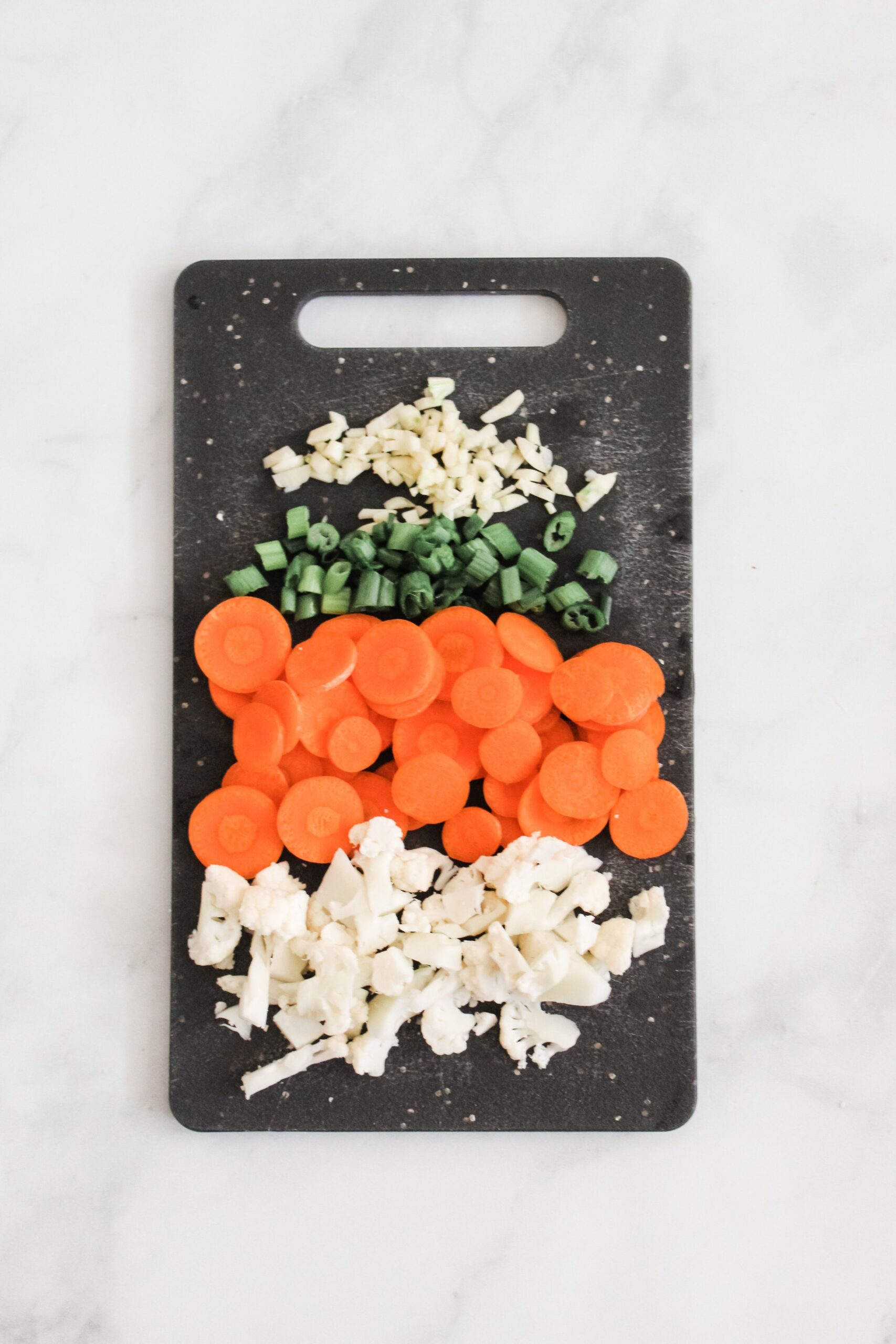 chopped up cauliflower, carrots, green onions, and ginger on black cutting board
